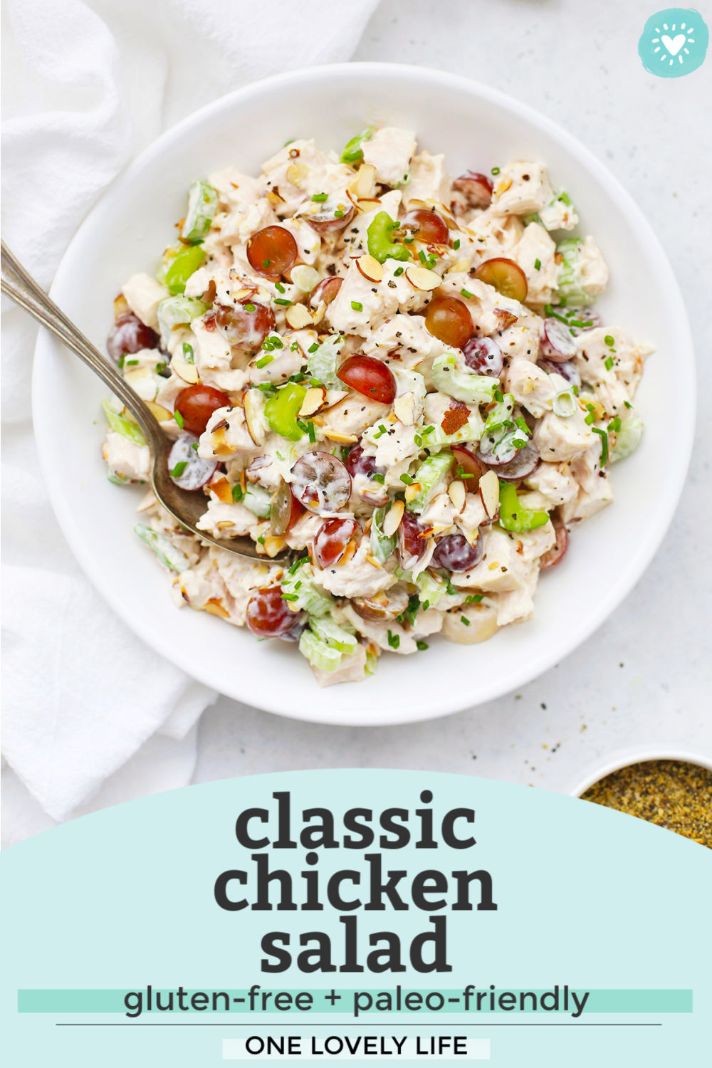 "Overhead view of a bowl of classic chicken salad with grapes in a white bowl with a white dish towel next to it with text overlay that reads ""Classic Chicken Salad. Gluten-Free + Paleo-Friendly. One Lovely Life"""