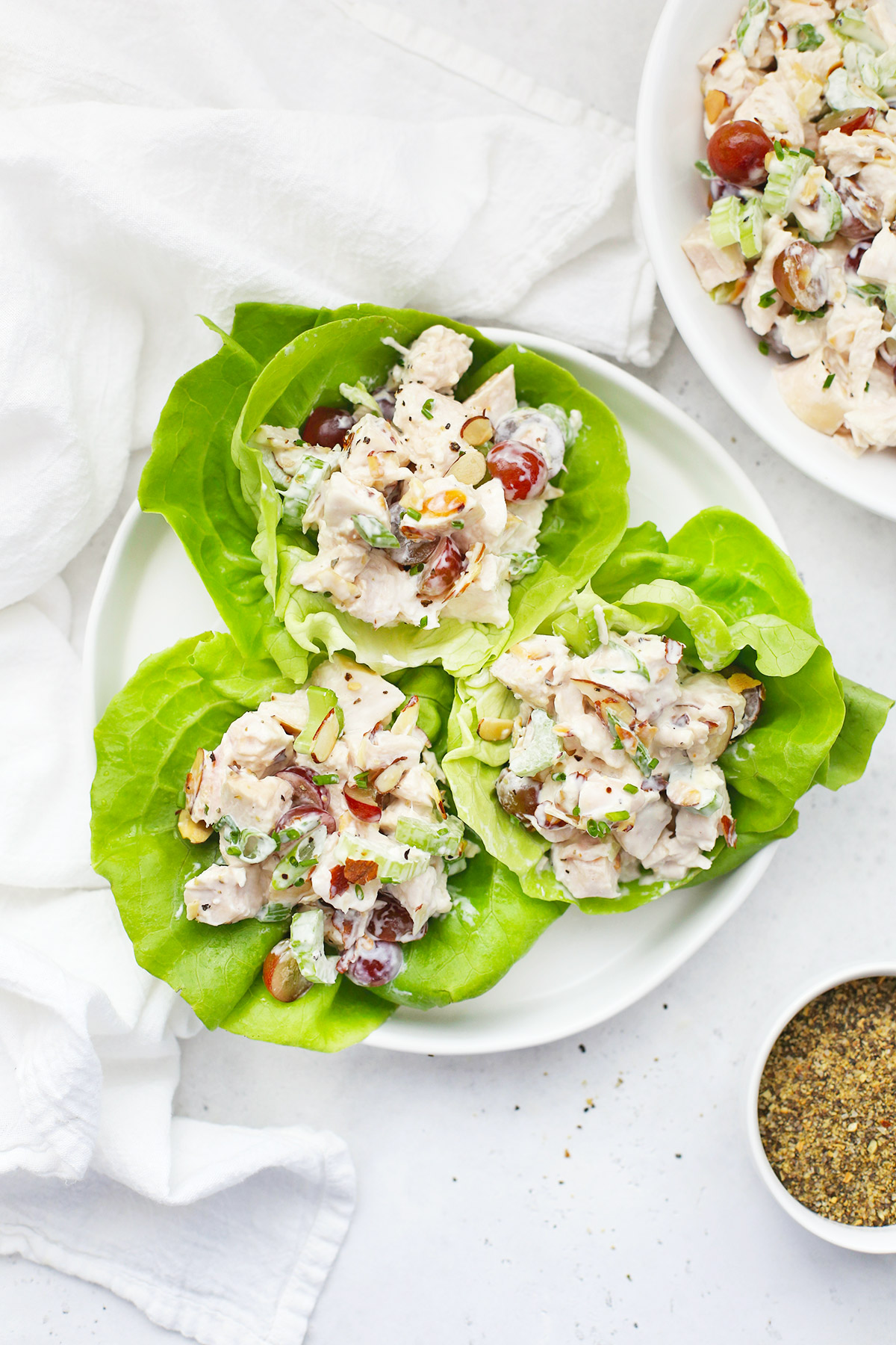 Three chicken salad lettuce wraps on a plate.