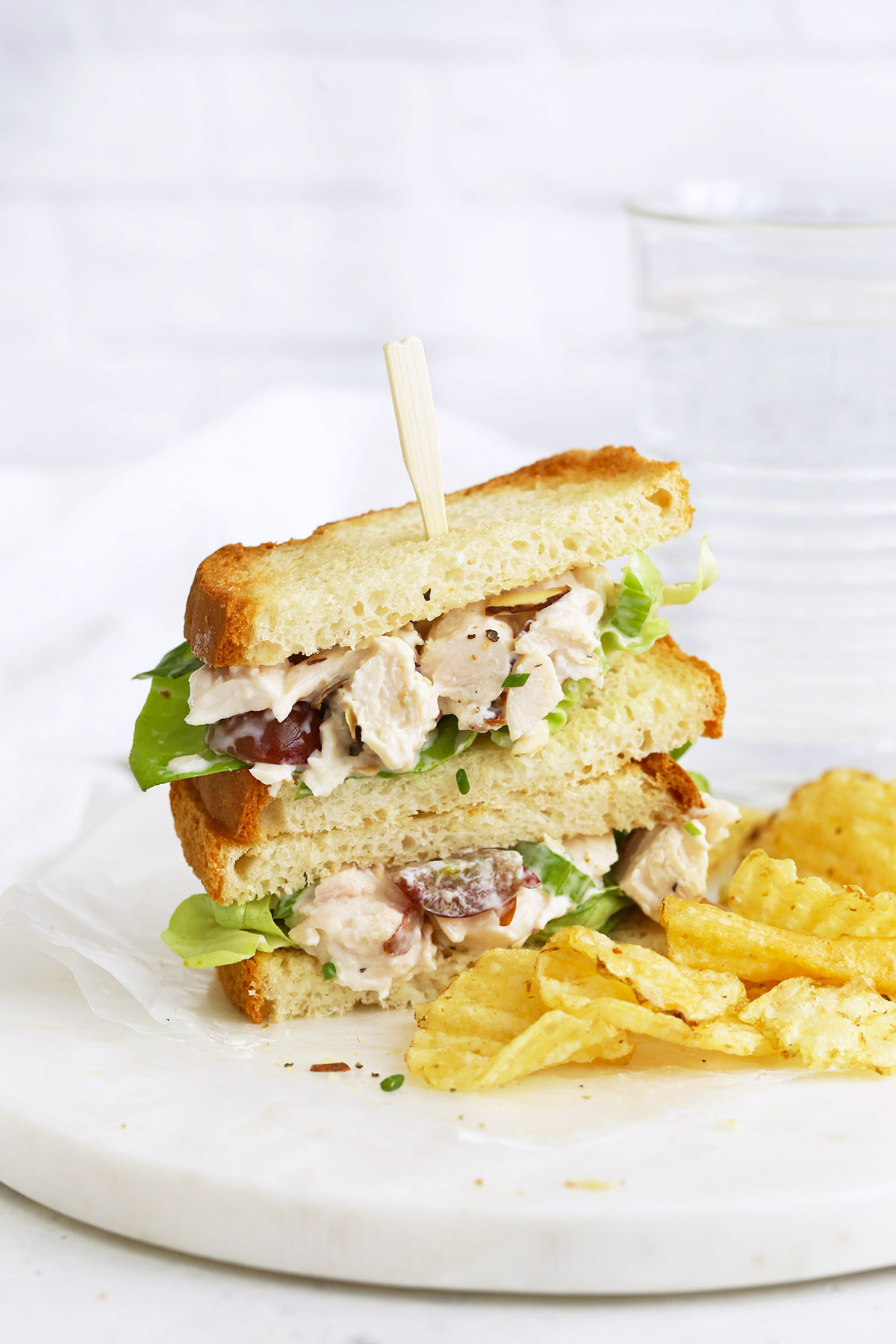 A gluten-free chicken salad sandwich on a marble serving board with kettle chips next to it.