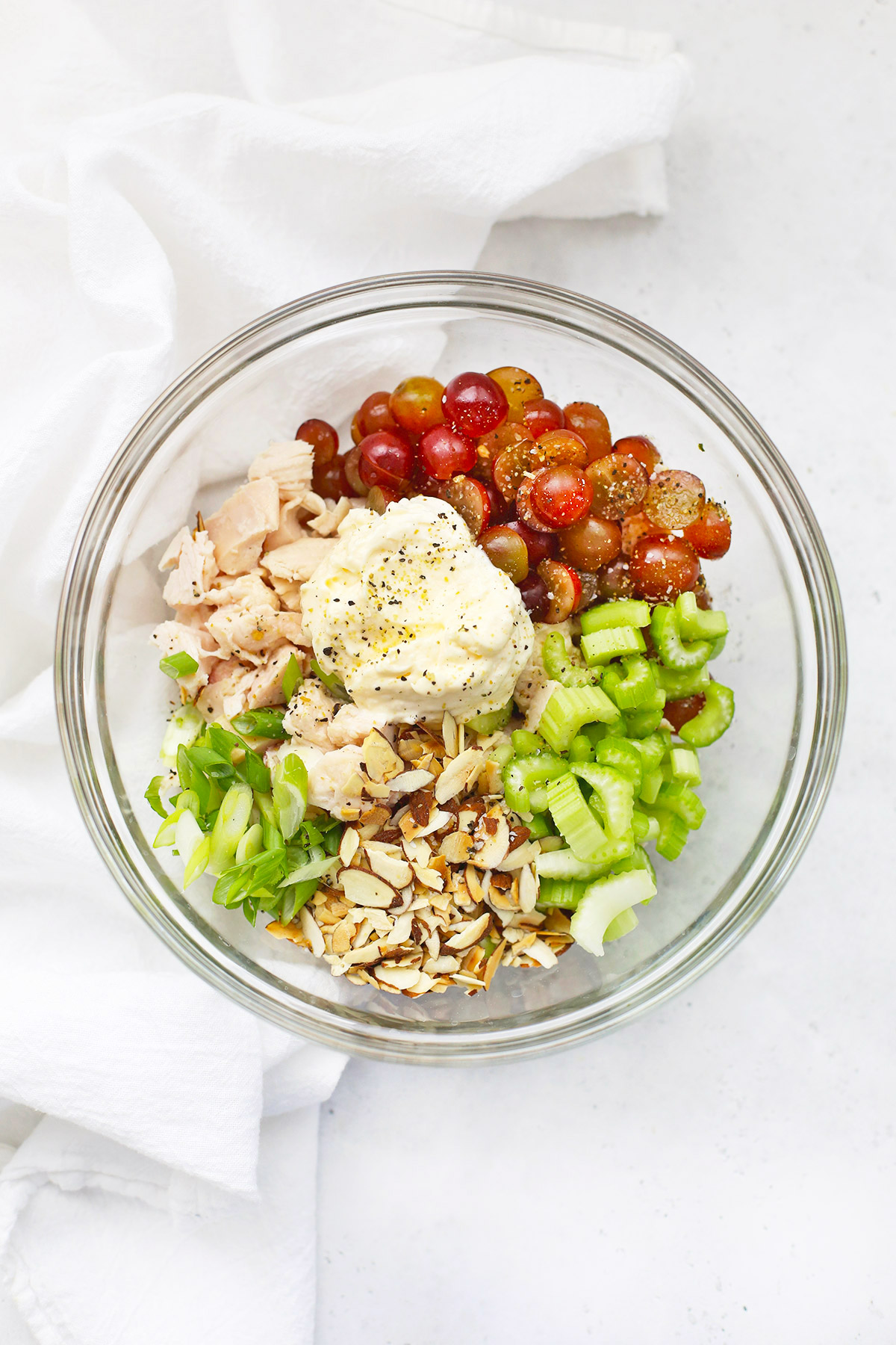 Chicken Salad Ingredients in a glass bowl with a white kitchen towel in the background
