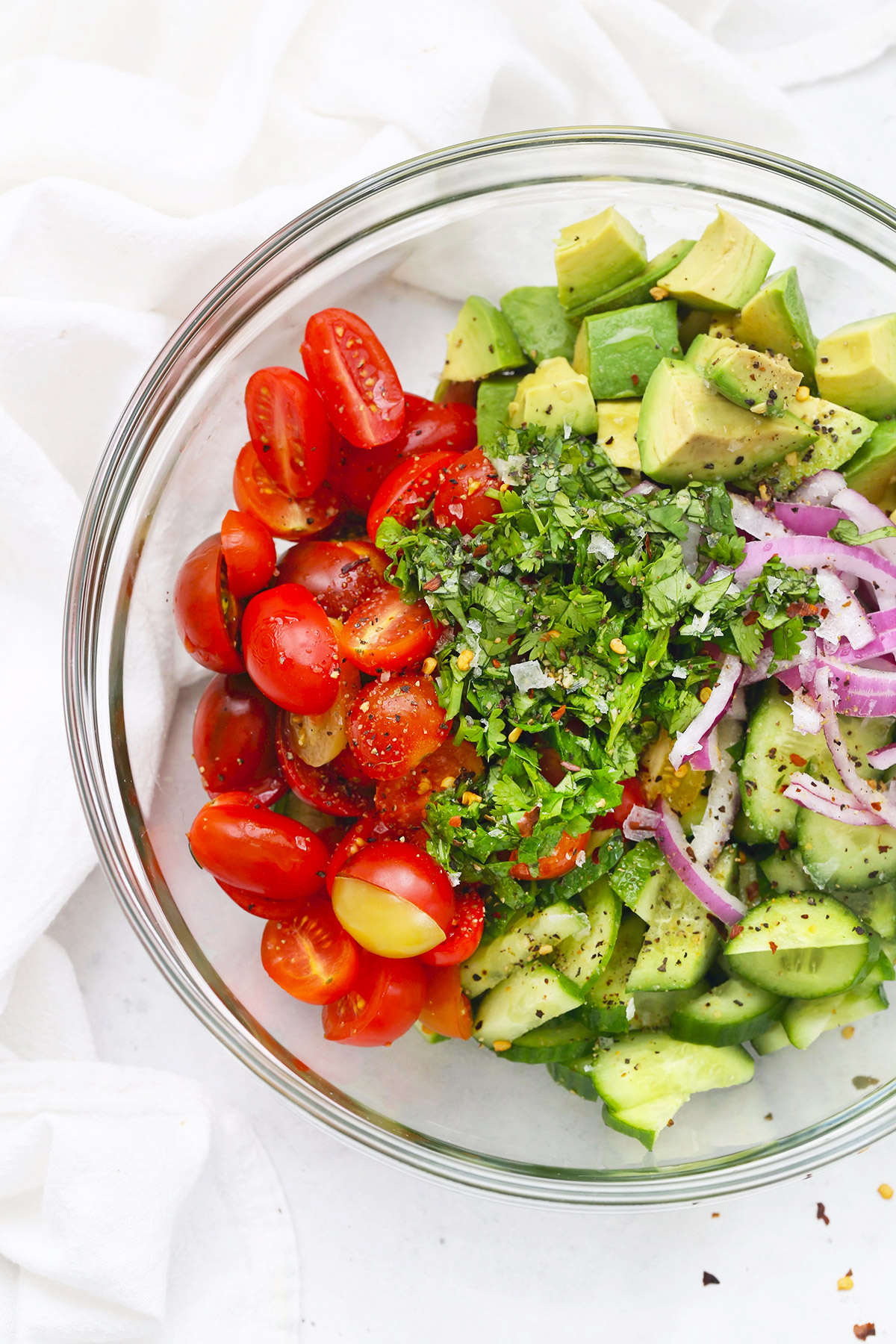 Glass bowl with ingredients for avocado, cucumber tomato salad.