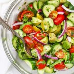 Close up overhead view of a glass bowl of avocado cucumber tomato salad