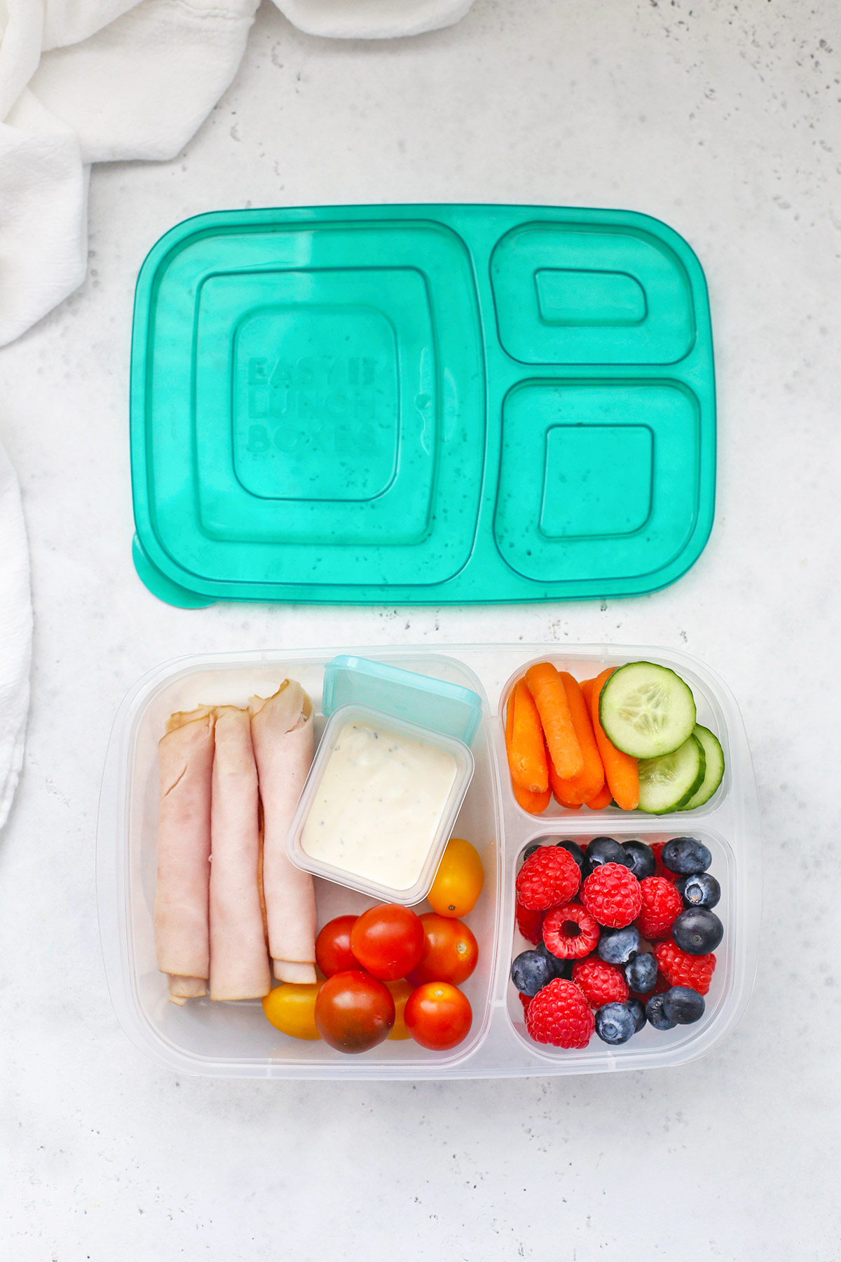 Easy Lunchbox with turkey roll-ups, ranch dressing, fresh veggies, and mixed berries
