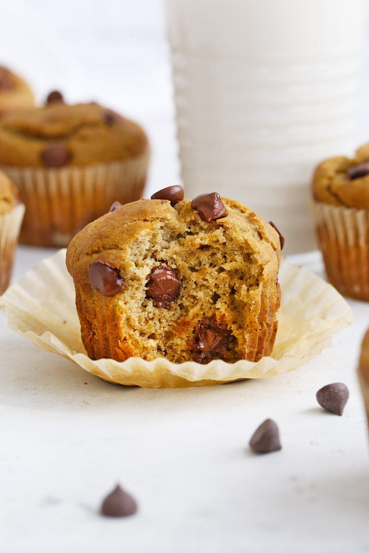 Gluten-Free Chocolate Chip Banana Muffins on a white background with chocolate chips scattered around them.