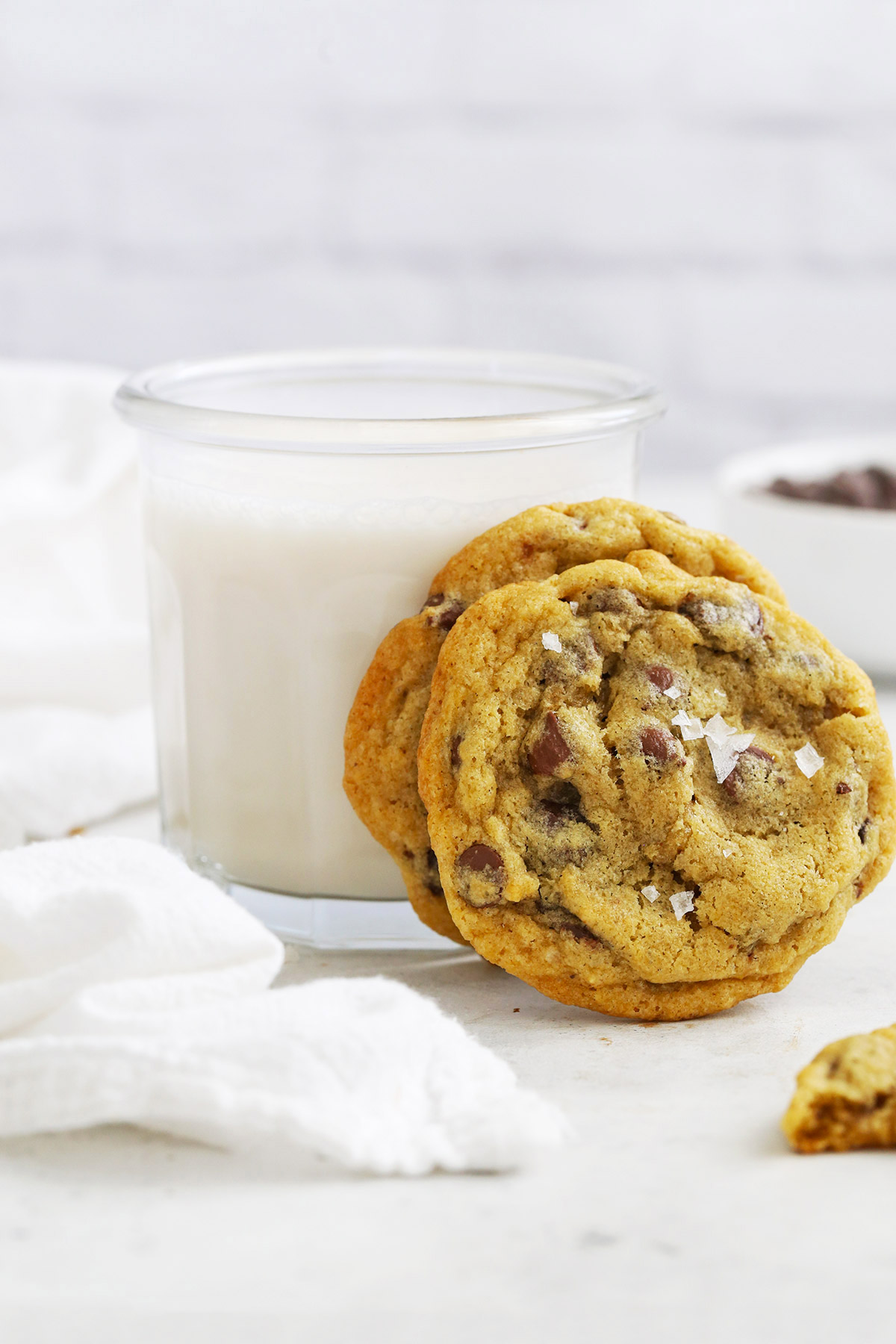 Gluten-Free Chocolate Chip Cookies leaning against a glass of almond milk