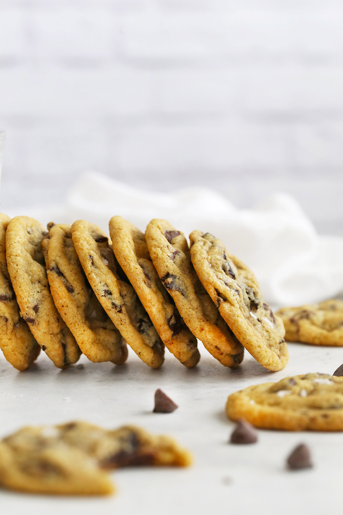 Gluten-Free Chocolate Chip Cookies leaning on each other with a white background