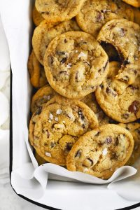 Close-up overhead photo of gluten free chocolate chip cookies in a white enamel pan