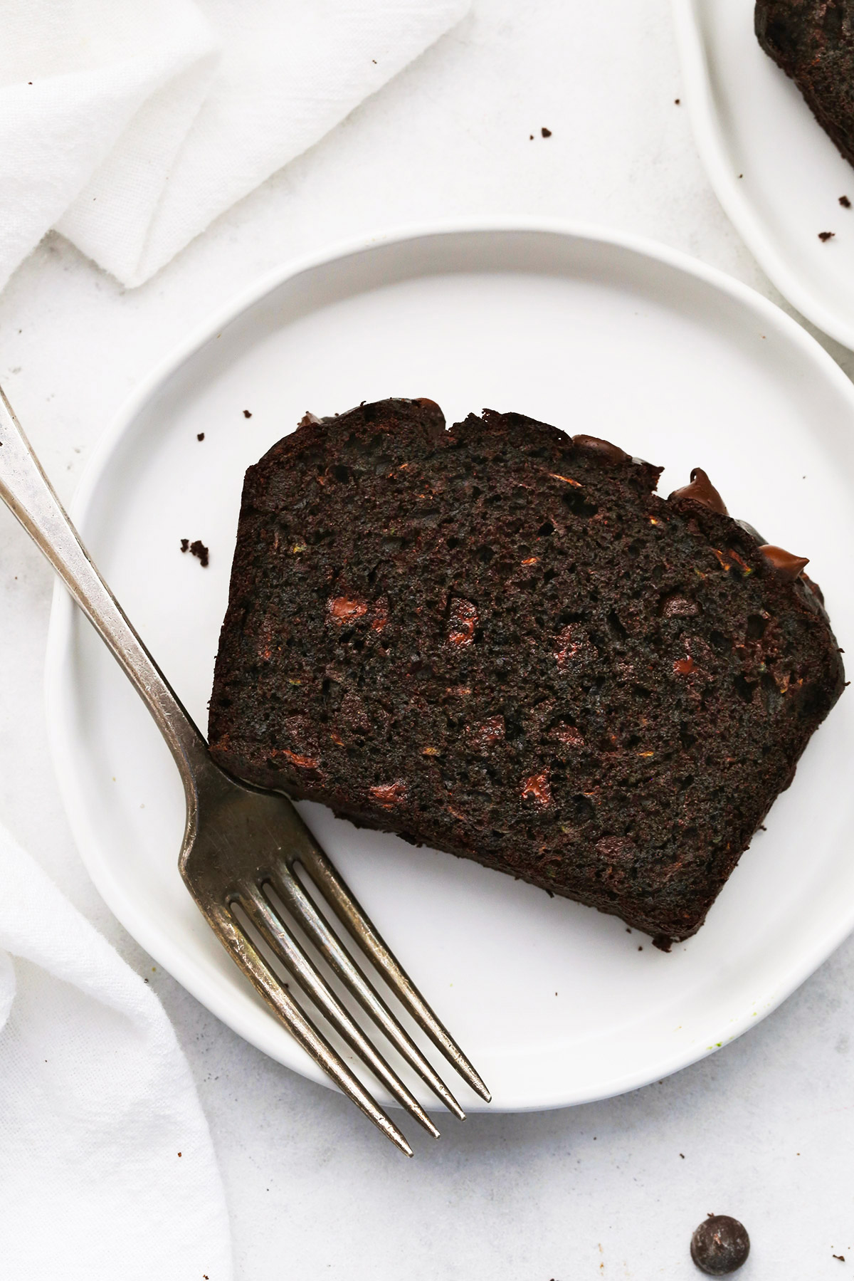 Close up view of a slice of gluten-free chocolate zucchini bread on a white plate