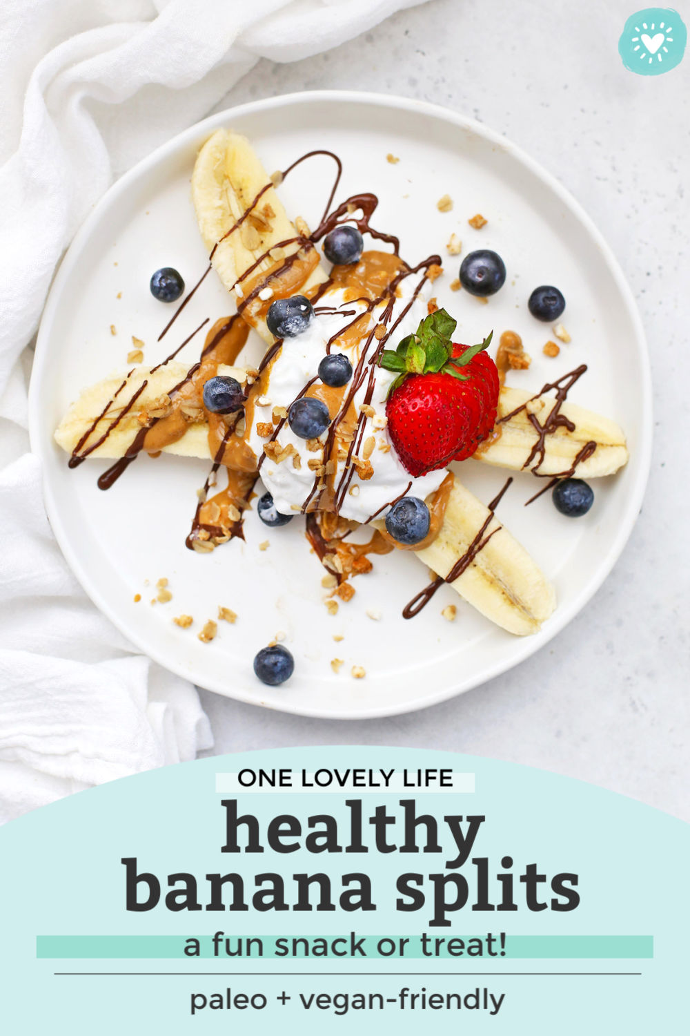 """Healthy Banana Split with Yogurt, Peanut Butter, Chocolate, and berries on a white plate with text that reads """"One Lovely Life. Healthy Banana Splits--a fun snack or treat! Paleo + vegan-friendly"""""""