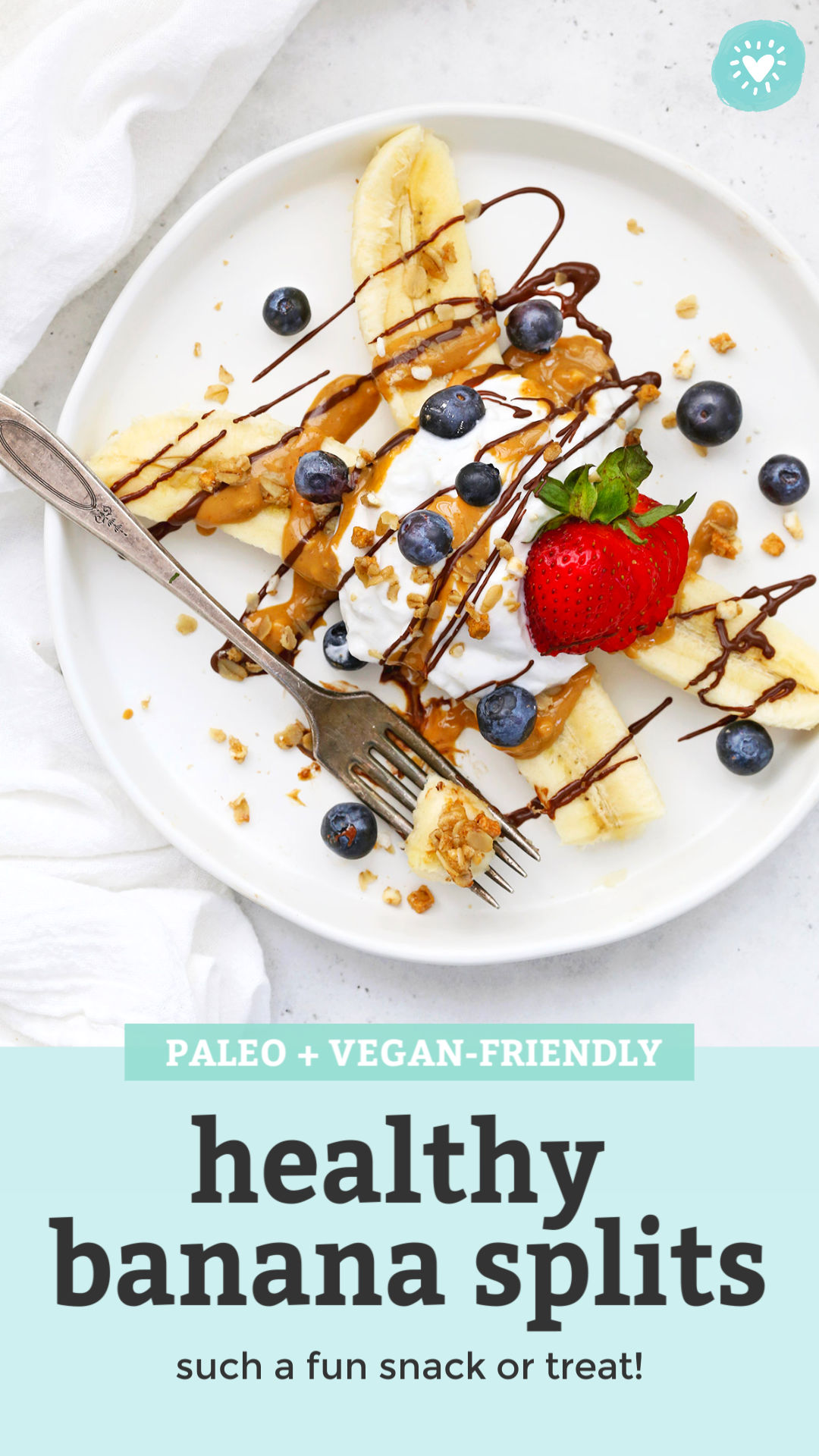 """Healthy Banana Split with Yogurt, Peanut Butter, Chocolate, and berries on a white plate with text overlay that reads """"Paleo + Vegan-Friendly Healthy Banana Splits. Such a fun snack or treat!"""""""