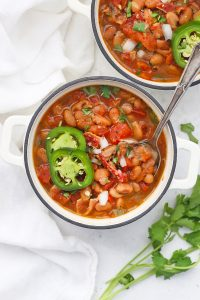Two bowls of Instant Pot Charro Beans on a white background