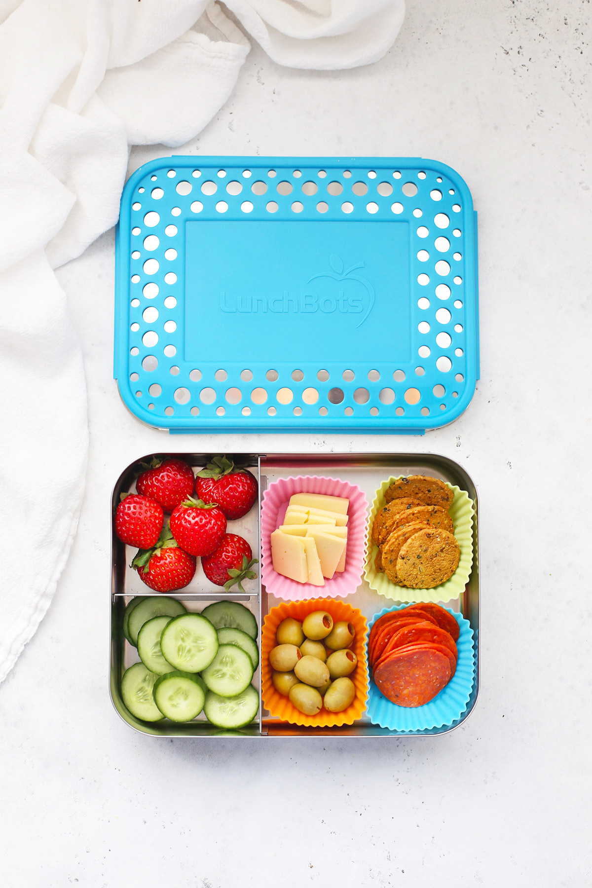 Lunchbots stainless steel large lunch box with strawberries, dairy-free cheese, gluten-free crackers, pepperoni, green olives, and cucumbers