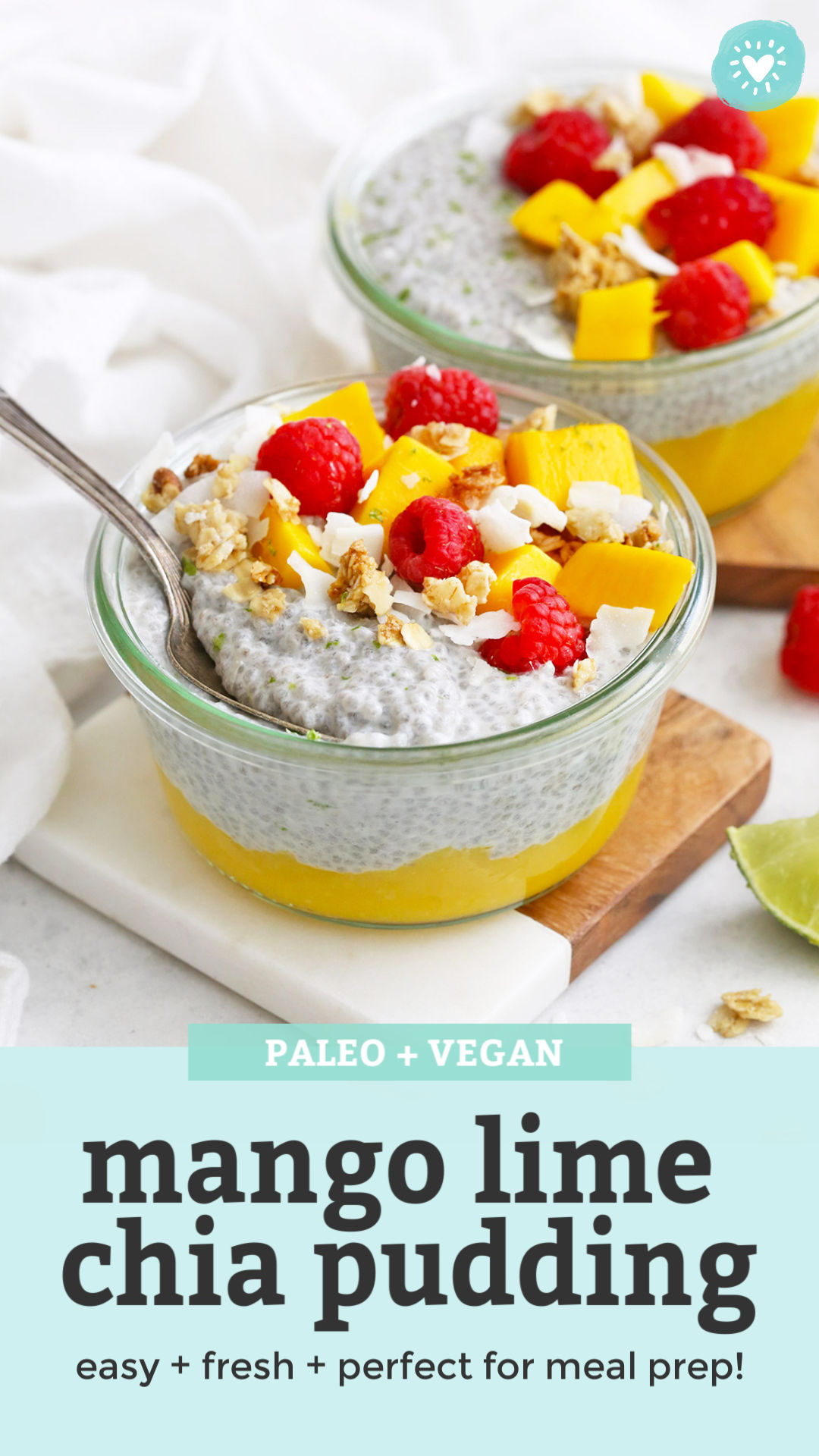 "Front View of Jars of Mango Chia Pudding Topped with Raspberries, Granola, and Fresh Mango with text that reads ""Paleo & Vegan Mango Lime Chia Pudding. Easy + Fresh + Perfect for meal prep!"""