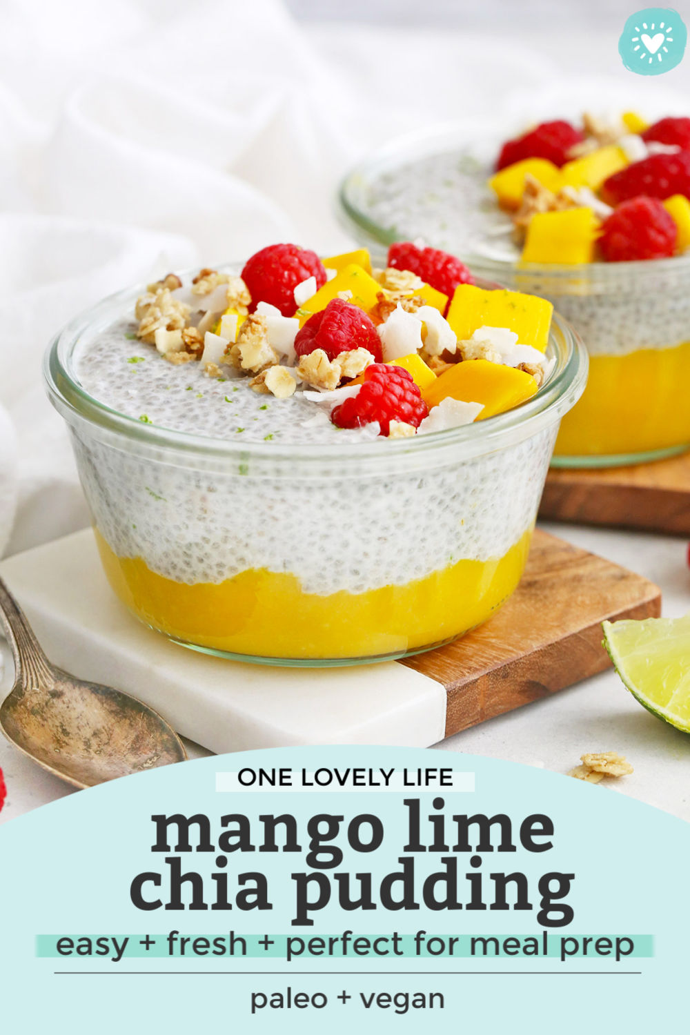 "Close Up Front View of Jars of Mango Chia Pudding Topped with Raspberries, Granola, and Fresh Mango with text that reads ""One Lovely Life. Mango Lime Chia Pudding. Easy + Fresh + Perfect for meal prep! Paleo + Vegan"""