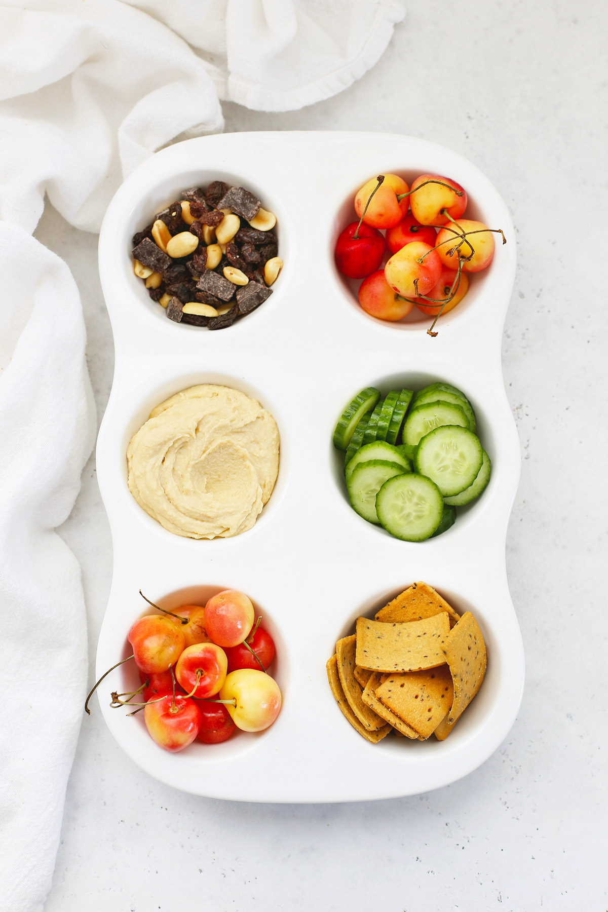 Muffin Tin Snack Tray for Kids with Trail Mix, Rainier Cherries, Hummus, Cucumber Slices, and Gluten-Free Crackers