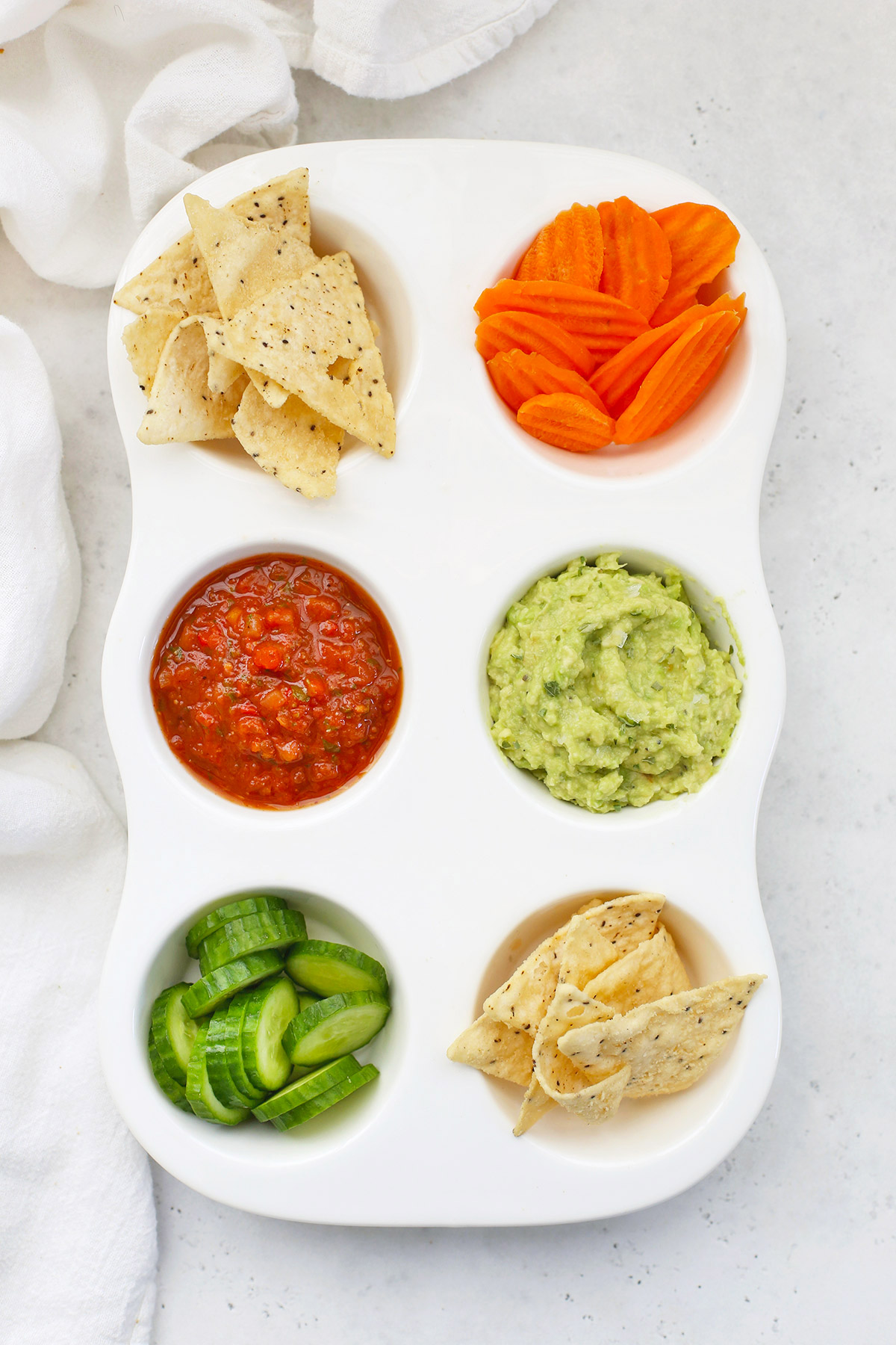 Muffin Tin Snack Tray For Kids with Grain-Free Tortilla Chips, Carrot Chips, Salsa, Guacamole, and Cucumber Slices