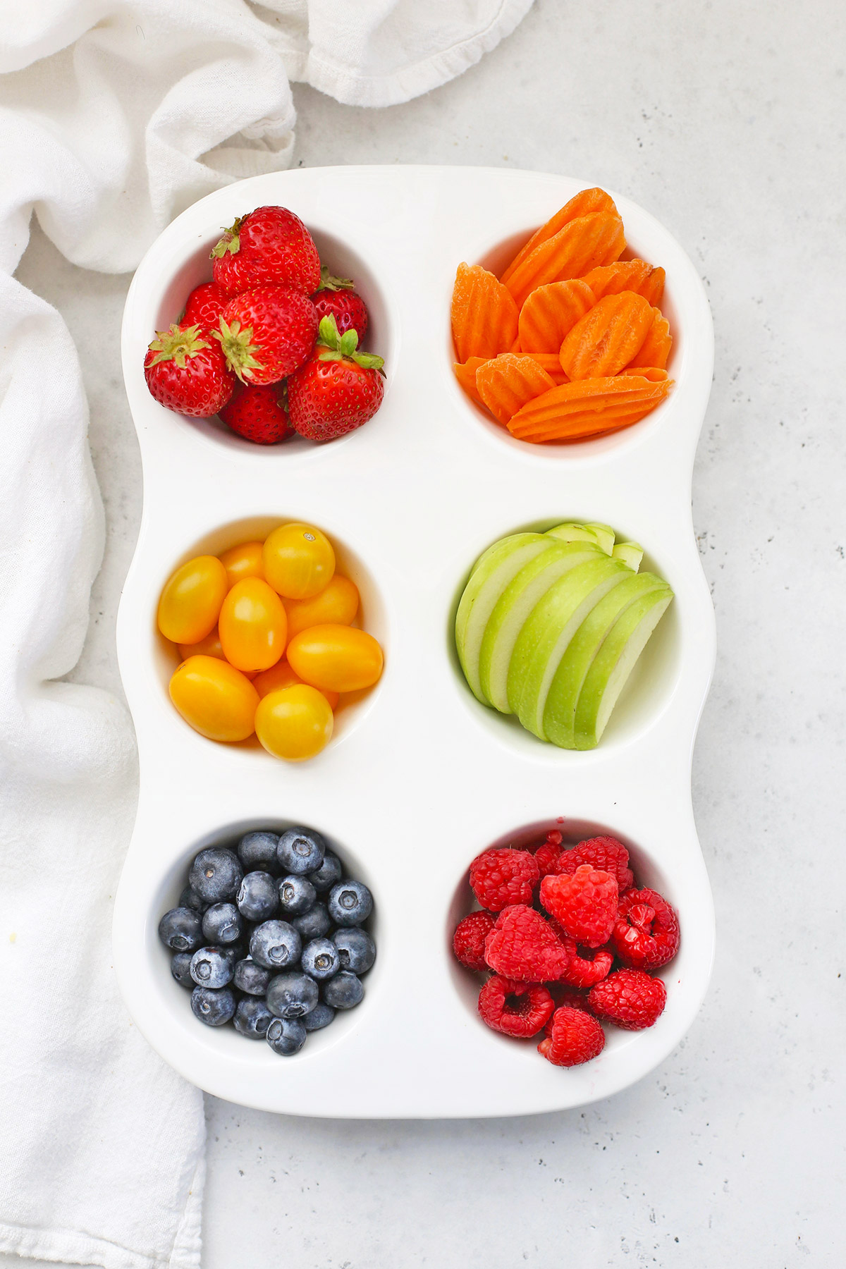 Rainbow Muffin Tin Snack Tray For Kids with Strawberries, Carrot Chips, Yellow Grape Tomatoes, Green Apple Slices, Blueberries, and Raspberries