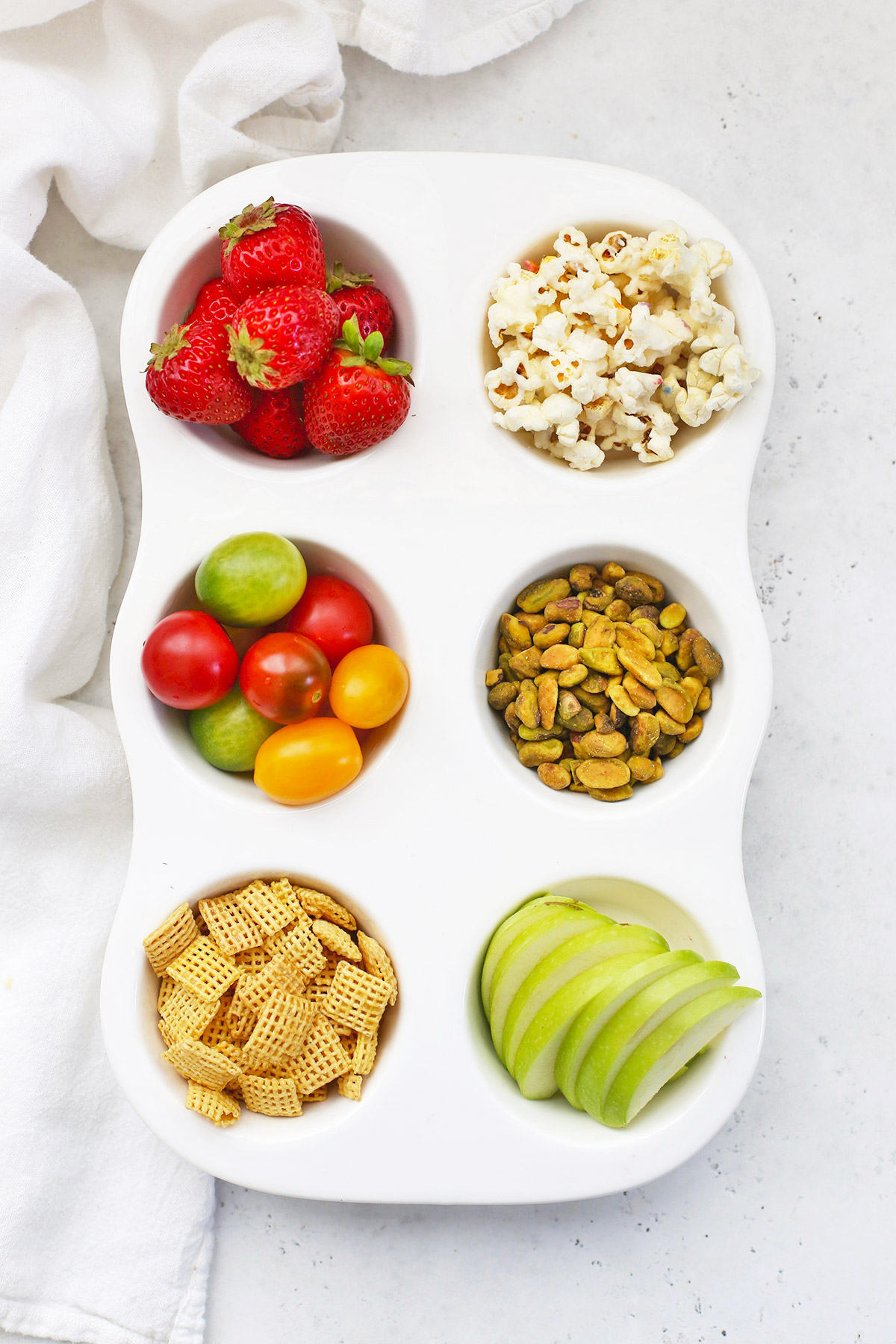 Muffin Tin Snack Tray For Kids with Strawberries, Popcorn, Grape Tomatoes, Pistachios, Gluten-Free Cereal, and Green Apple Slices