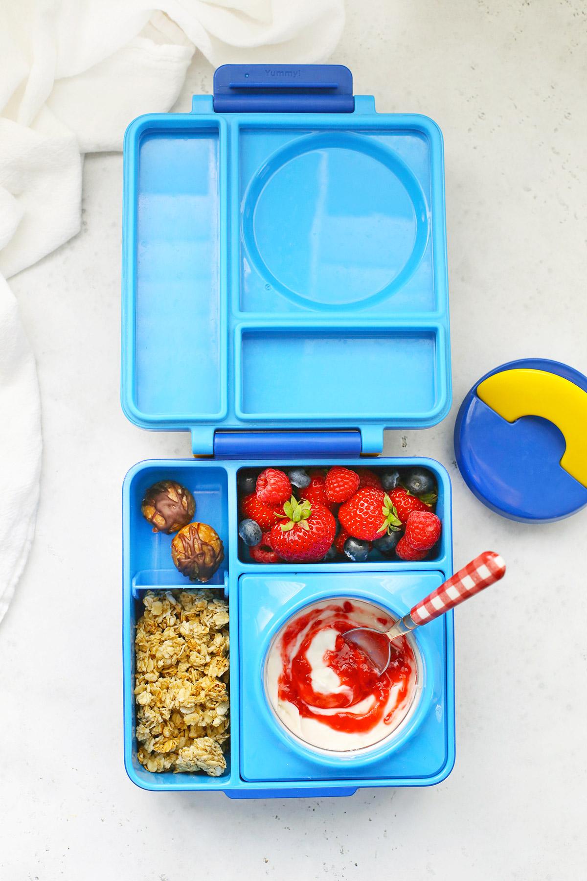 Blue Omie Box with yogurt, raspberry sauce, gluten-free granola, energy bites, and fresh strawberries