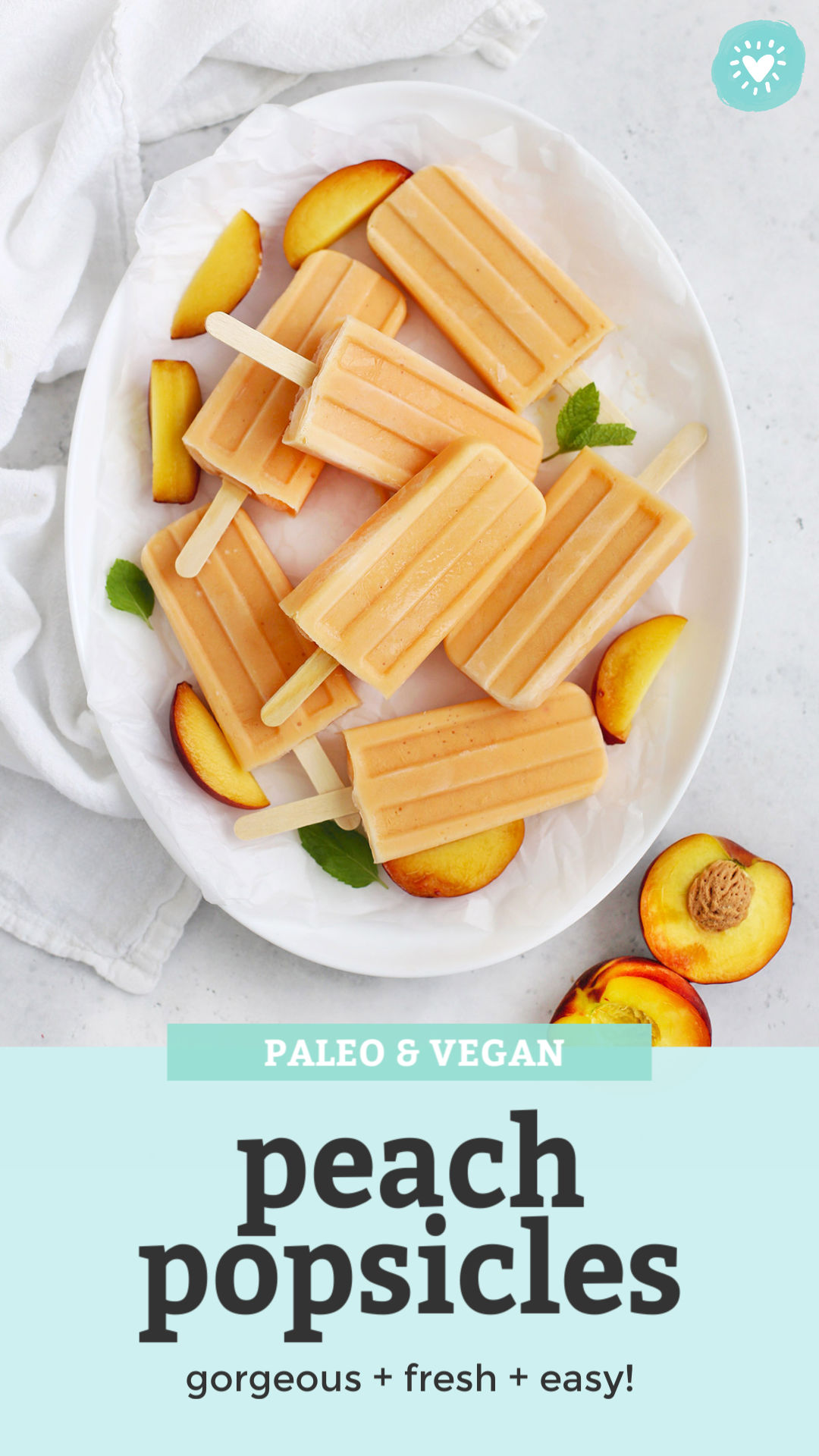 "overhead view of Peach Popsicles on a white platter with peach slices and mint leaves with text overlay that reads ""Paleo + Vegan Peach Popsicles. Gorgeous + fresh + easy!"""