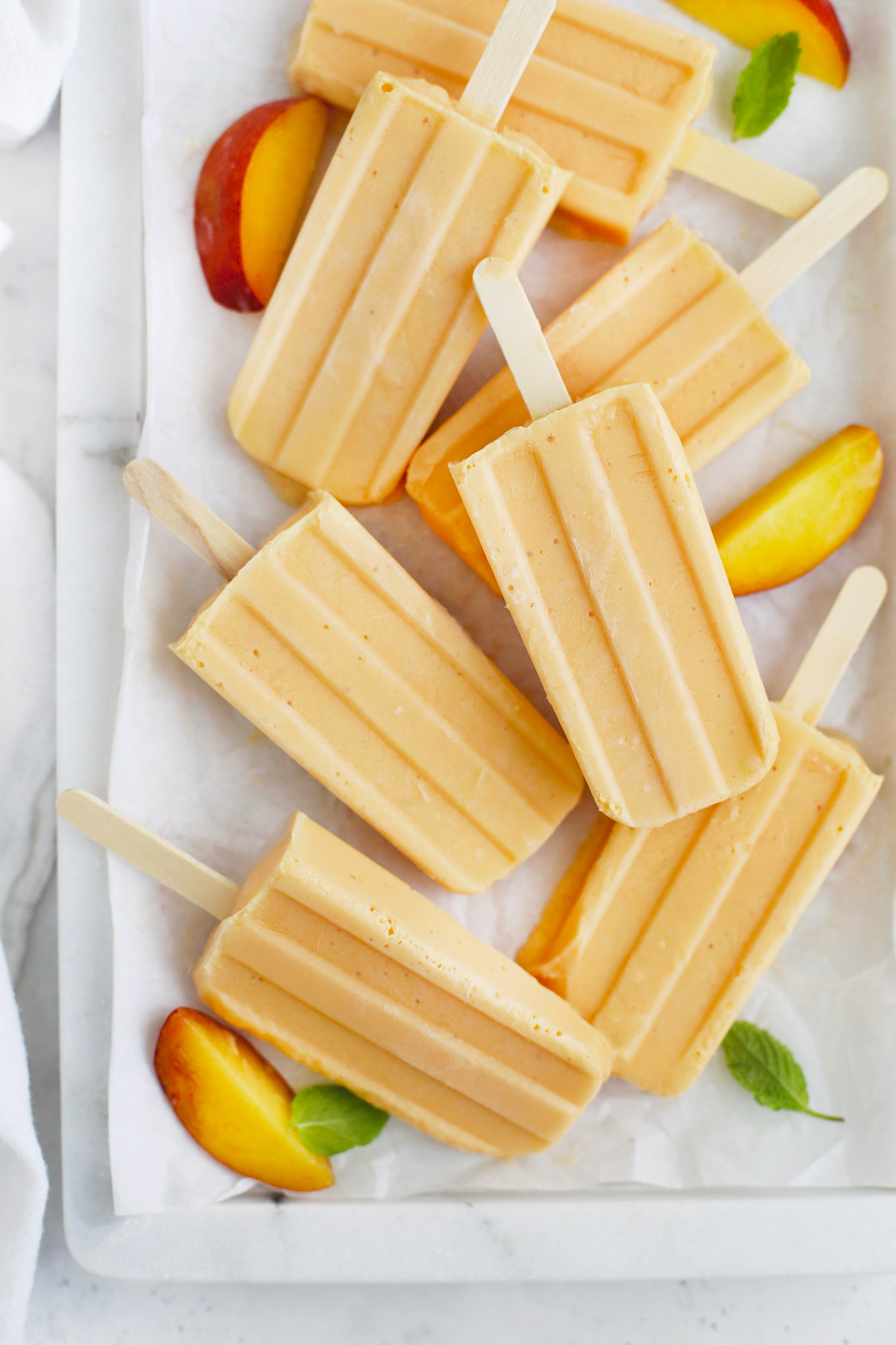 Overhead view of peach popsicles on a marble serving platter with peach slices and mint leaves