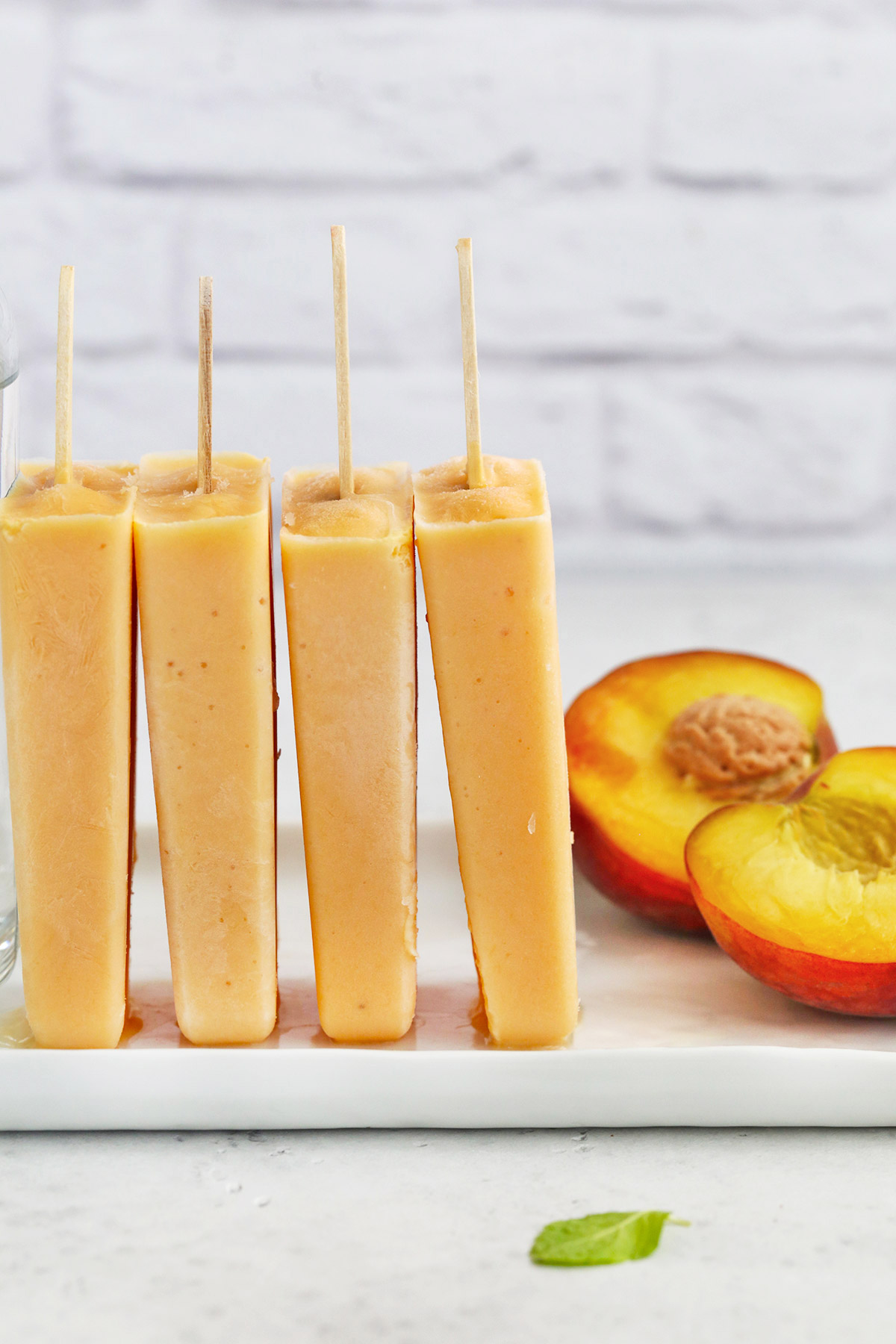 Peach Popsicles upright leaning on each other with a split peach in the background