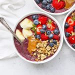 Three Peanut Butter Acai Bowls topped with fresh berries, banana, granola, and peanut butter.