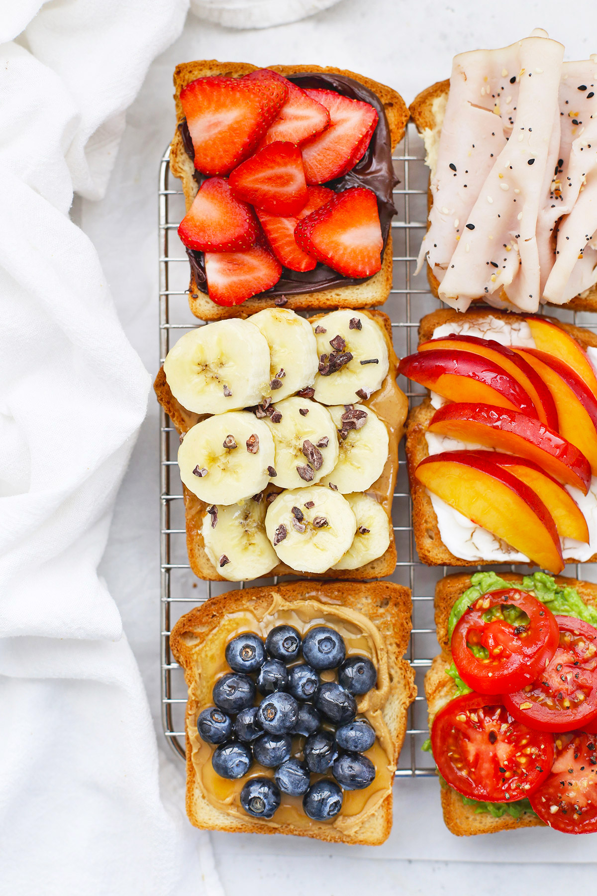 Close up view of six Slices of Gluten-Free toast with different toppings on a wire cooling rack
