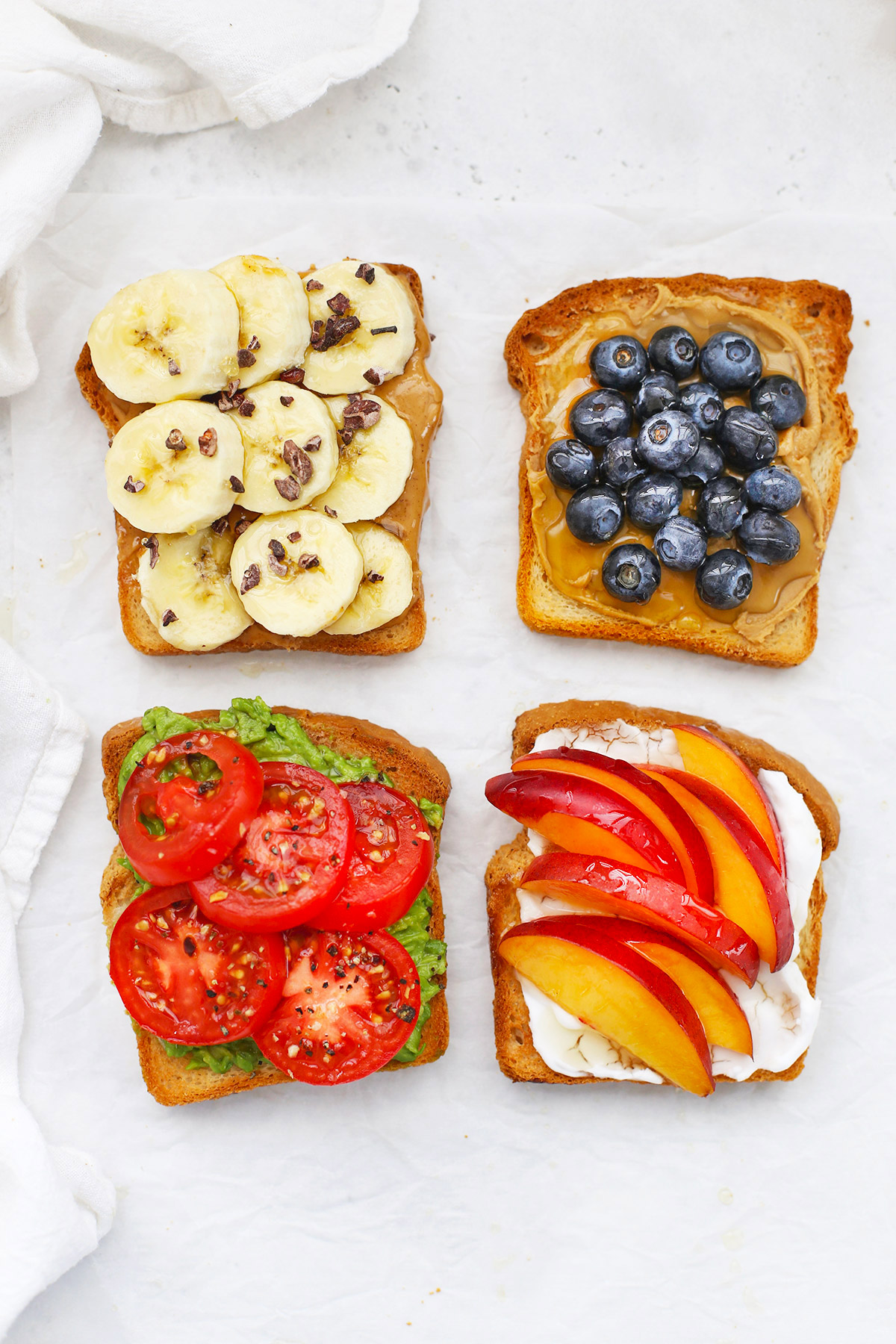 Four slices of gluten-free toast with different toppings on a white background.