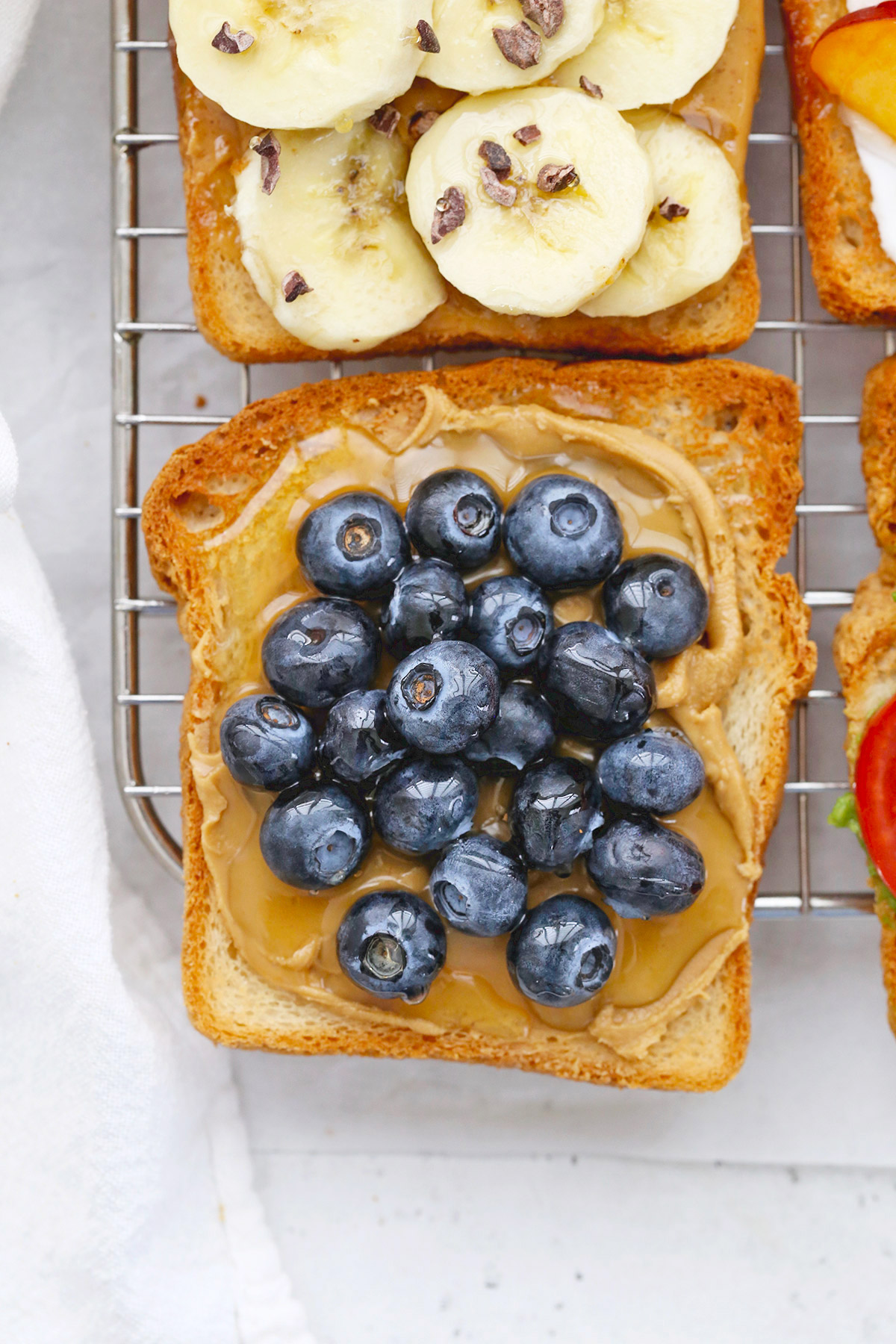 Close up view of gluten-free toast with almond butter, blueberries, and honey on a cooling rack