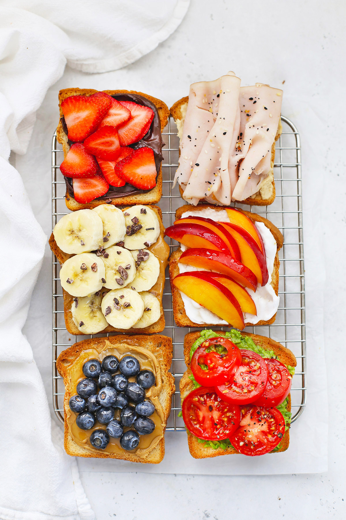 Overhead view of six Slices of Gluten-Free toast with different toppings on a wire cooling rack