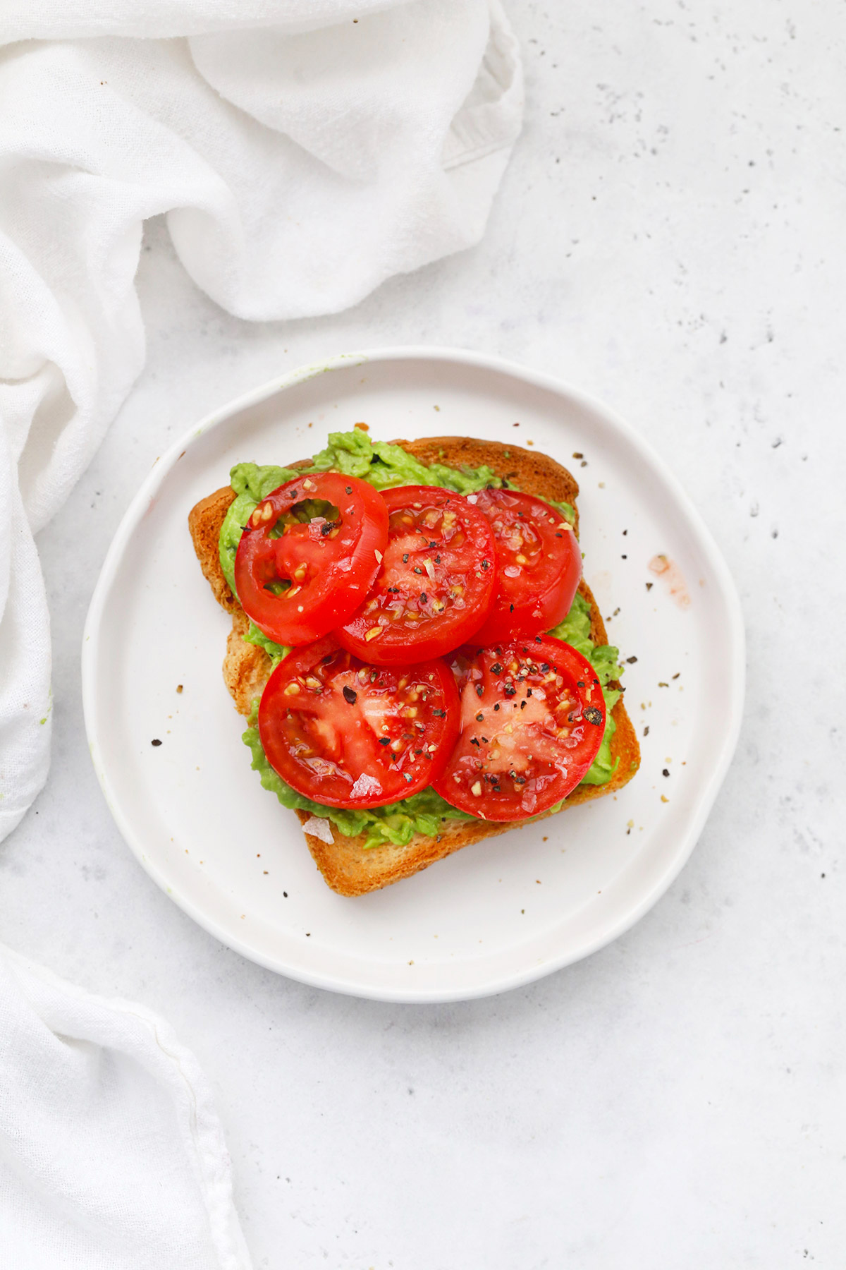 Gluten Free Avocado Toast with Tomatoes, and salt and pepper.