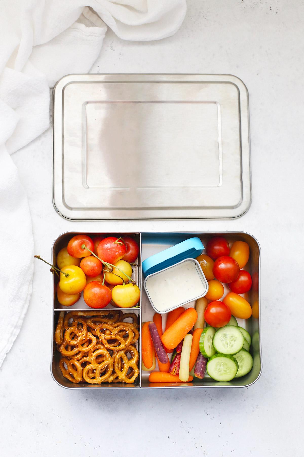 WeeSprout Stainless steel bento box with rainier cherries, gluten-free pretzels, ranch dip, and fresh veggies
