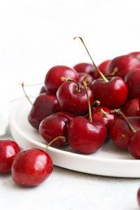 Close up view of sweet cherries on a white plate with a white background.