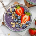 Close up view of a jar of paleo blueberry chia pudding topped with berries and granola