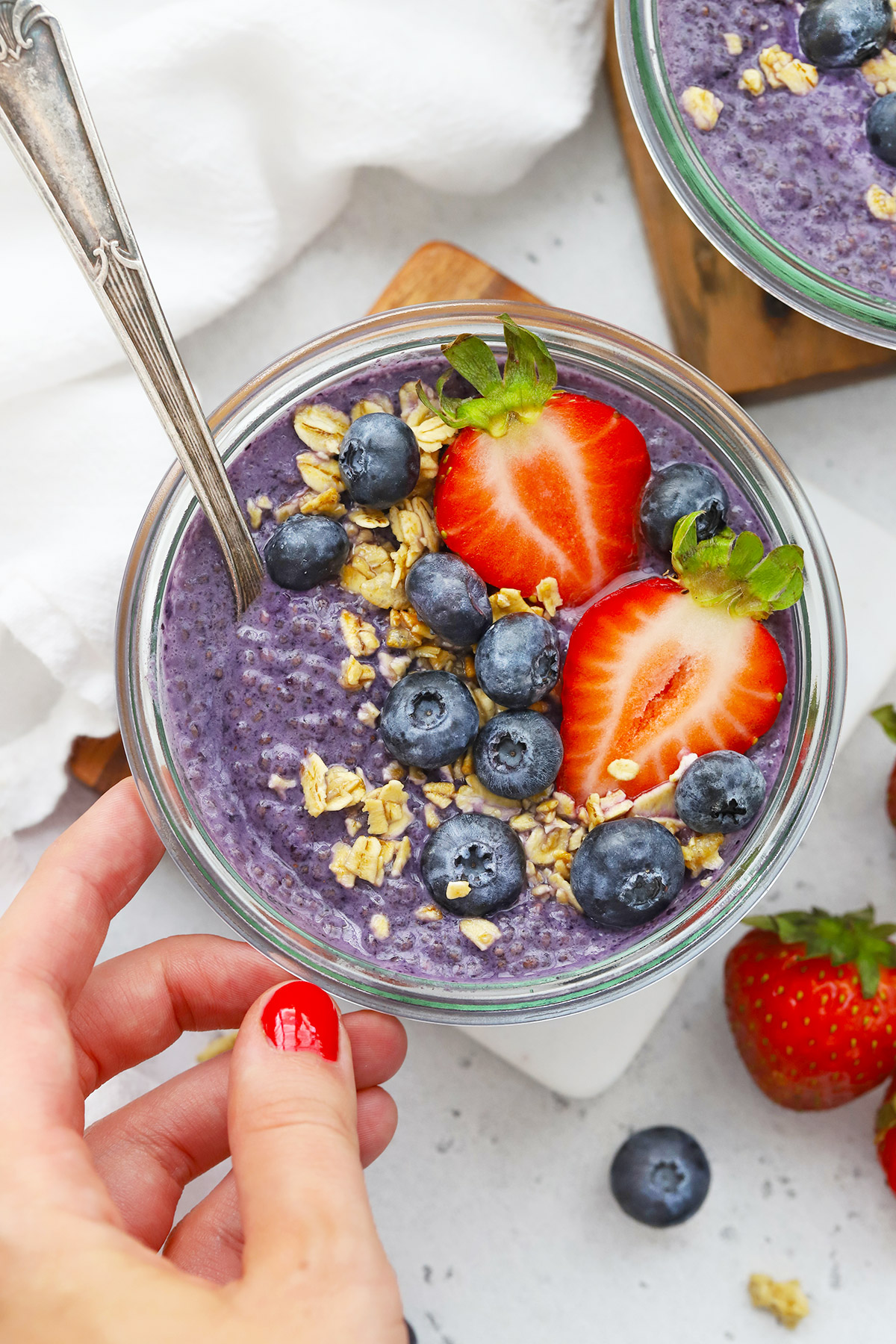 Setting down a jar of paleo blueberry chia pudding topped with berries and granola