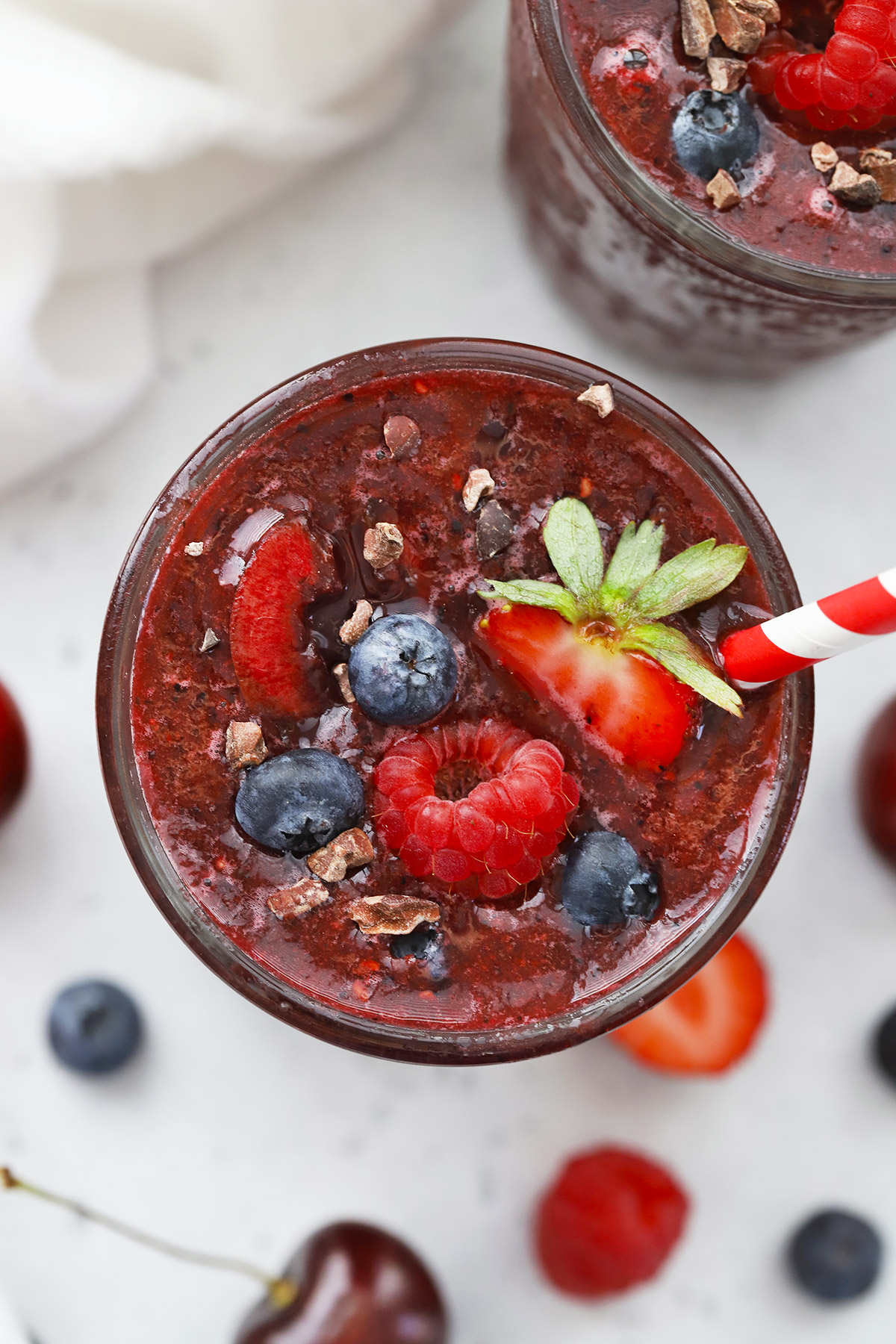 Close up view of a glass of vegan Cherry Berry Smoothie topped with fresh berries and cacao nibs