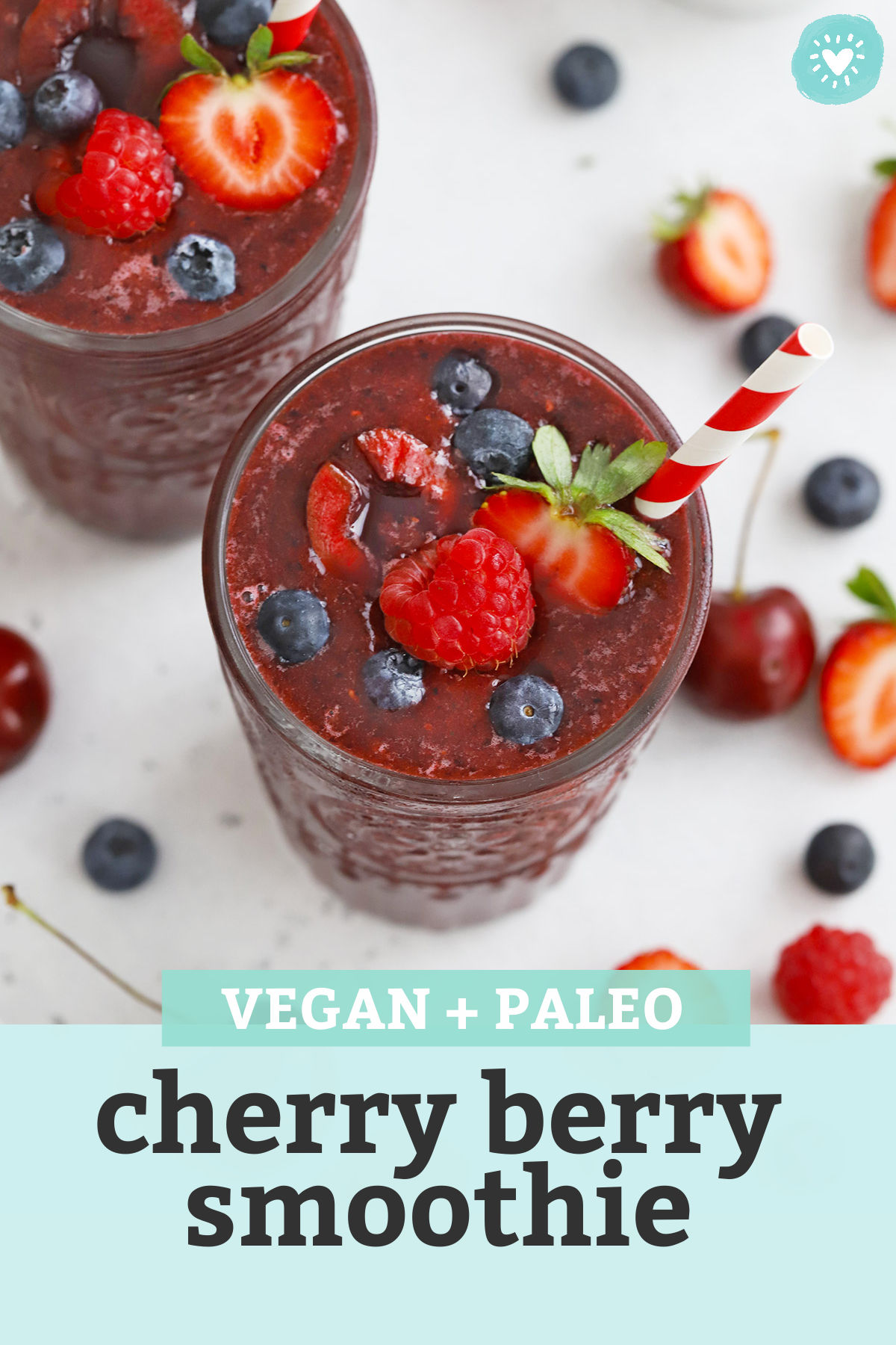 """Cherry Berry Smoothies topped with fresh berries and red and white stripe straws with text overlay that reads """"Vegan + Paleo Cherry Berry Smoothie"""""""