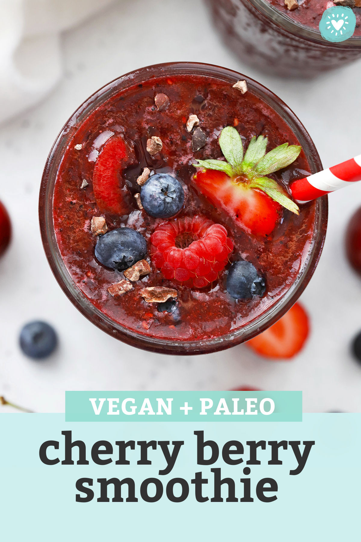 """Close up view of a glass of vegan Cherry Berry Smoothie topped with fresh berries and cacao nibs with text overlay that reads """"Vegan + Paleo Cherry Berry Smoothie"""""""