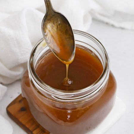 Spoon Drizzling Apple Cider Caramel Sauce into a jar