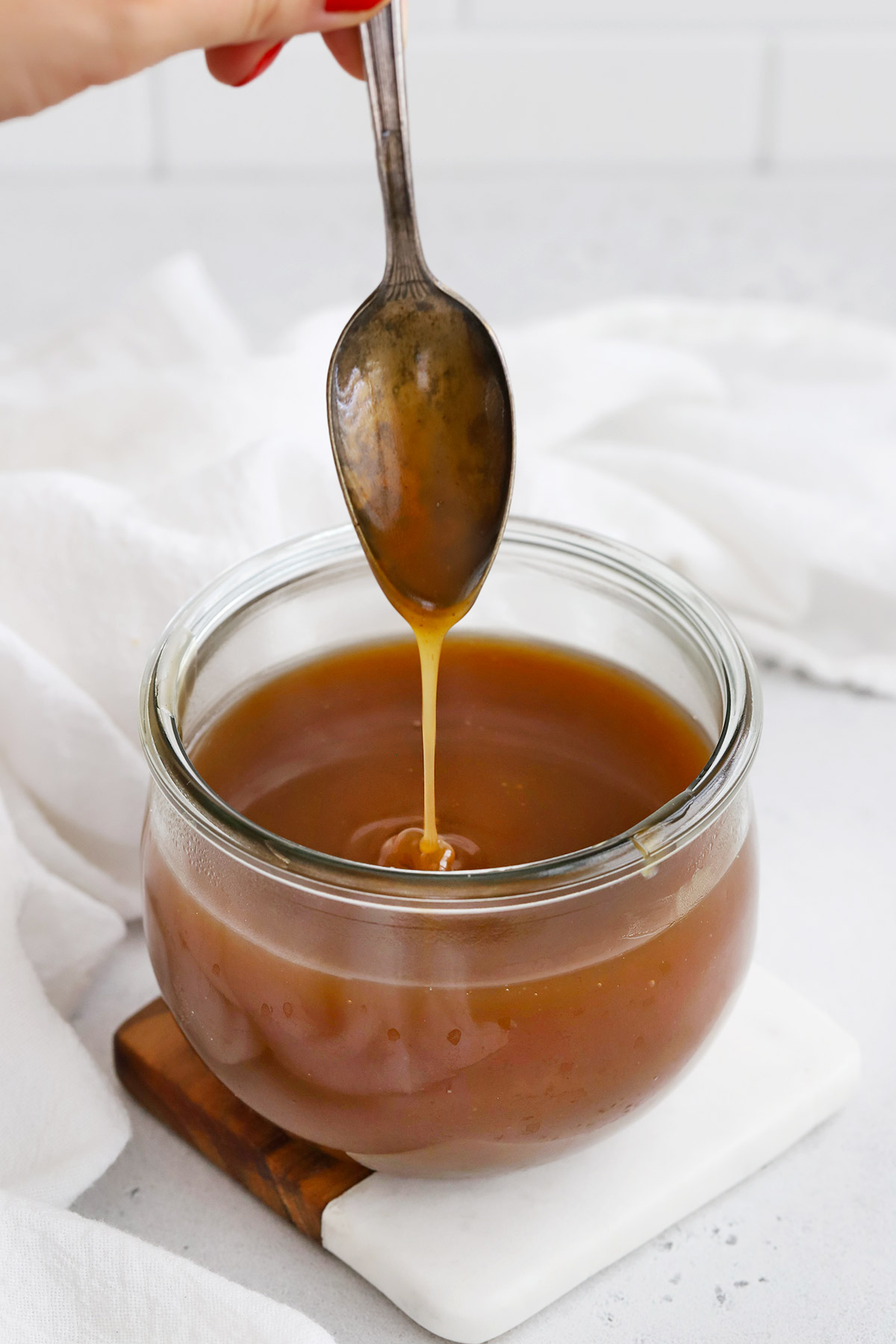 Spoon drizzling Vegan Apple Cider Caramel Sauce