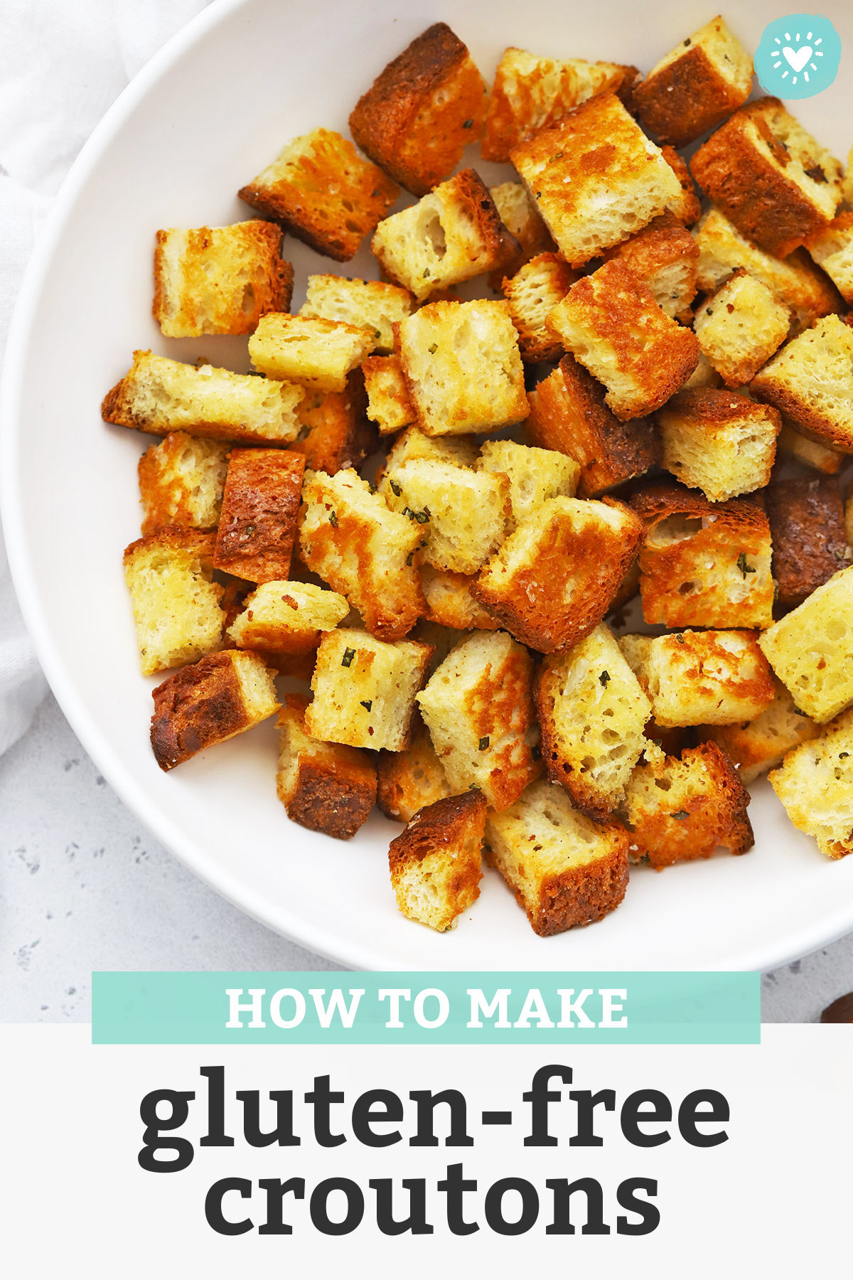 "Close up view of gluten-free croutons in a white bowl with text overlay that reads ""How to Make Gluten-Free Croutons"""