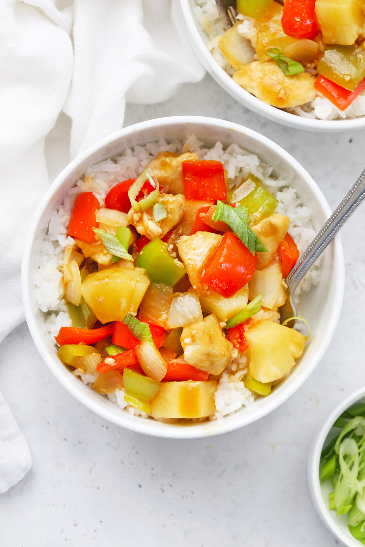 Paleo-Friendly Healthy Sweet and Sour Chicken in a white bowl on a white background