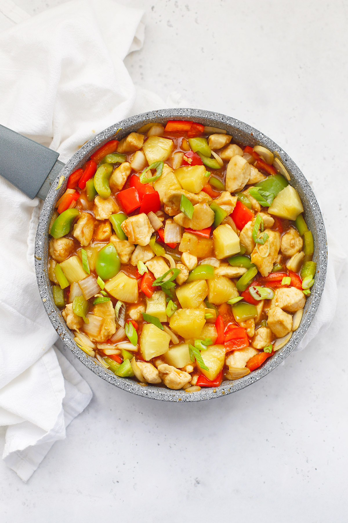 A pan full of Healthy Sweet and Sour Chicken on a white background