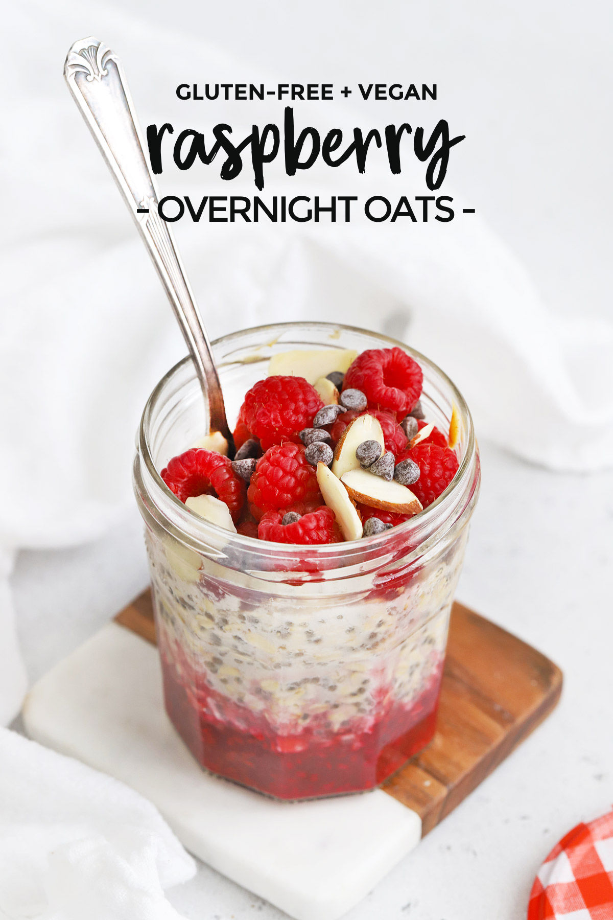 "Front view of a jar of raspberry overnight oats topped with sliced almonds and chocolate with text overlay that reads ""Raspberry Overnight Oats"""