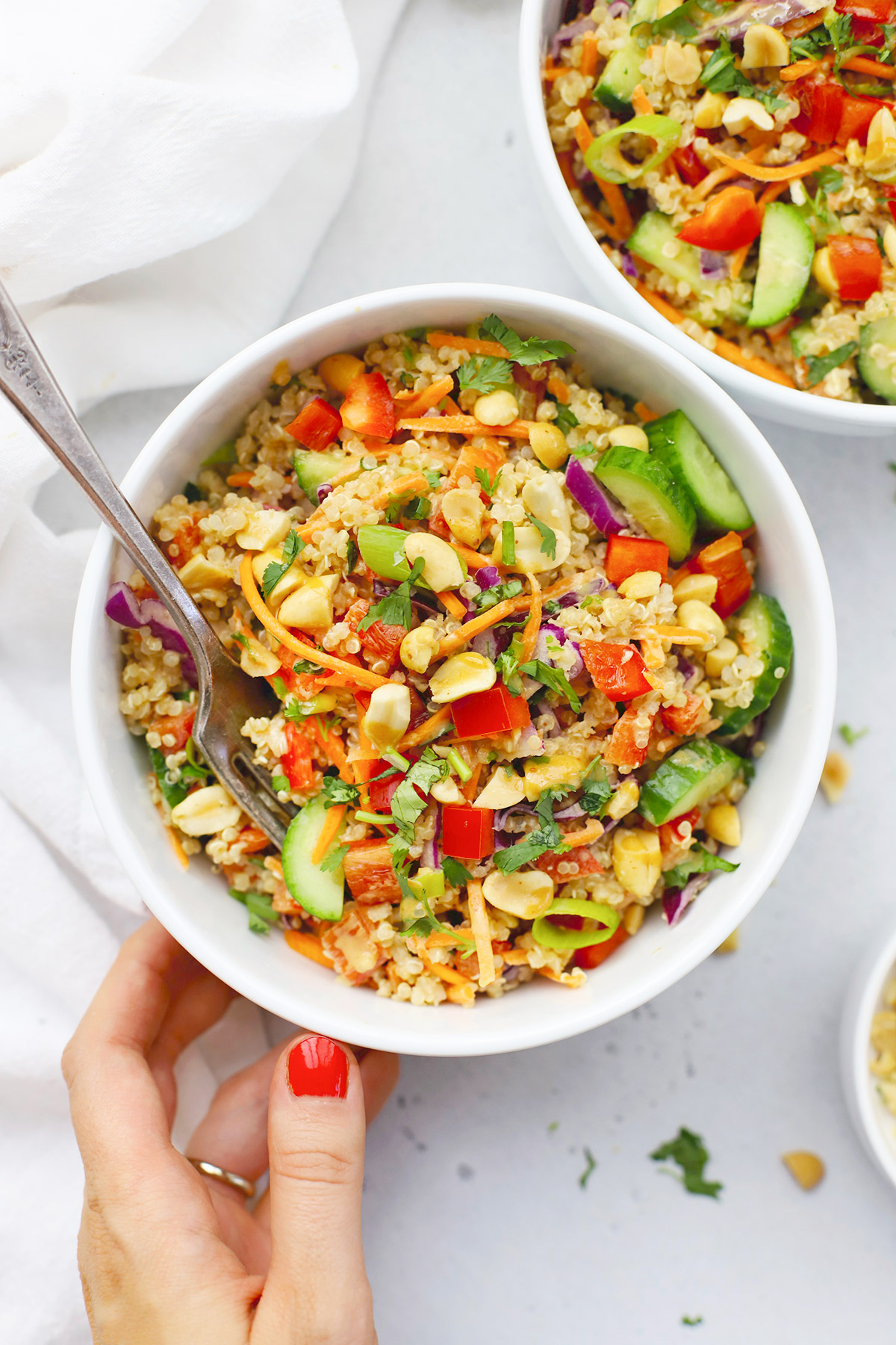 Setting down two bowls of Thai Quinoa Salad with Peanut Dressing