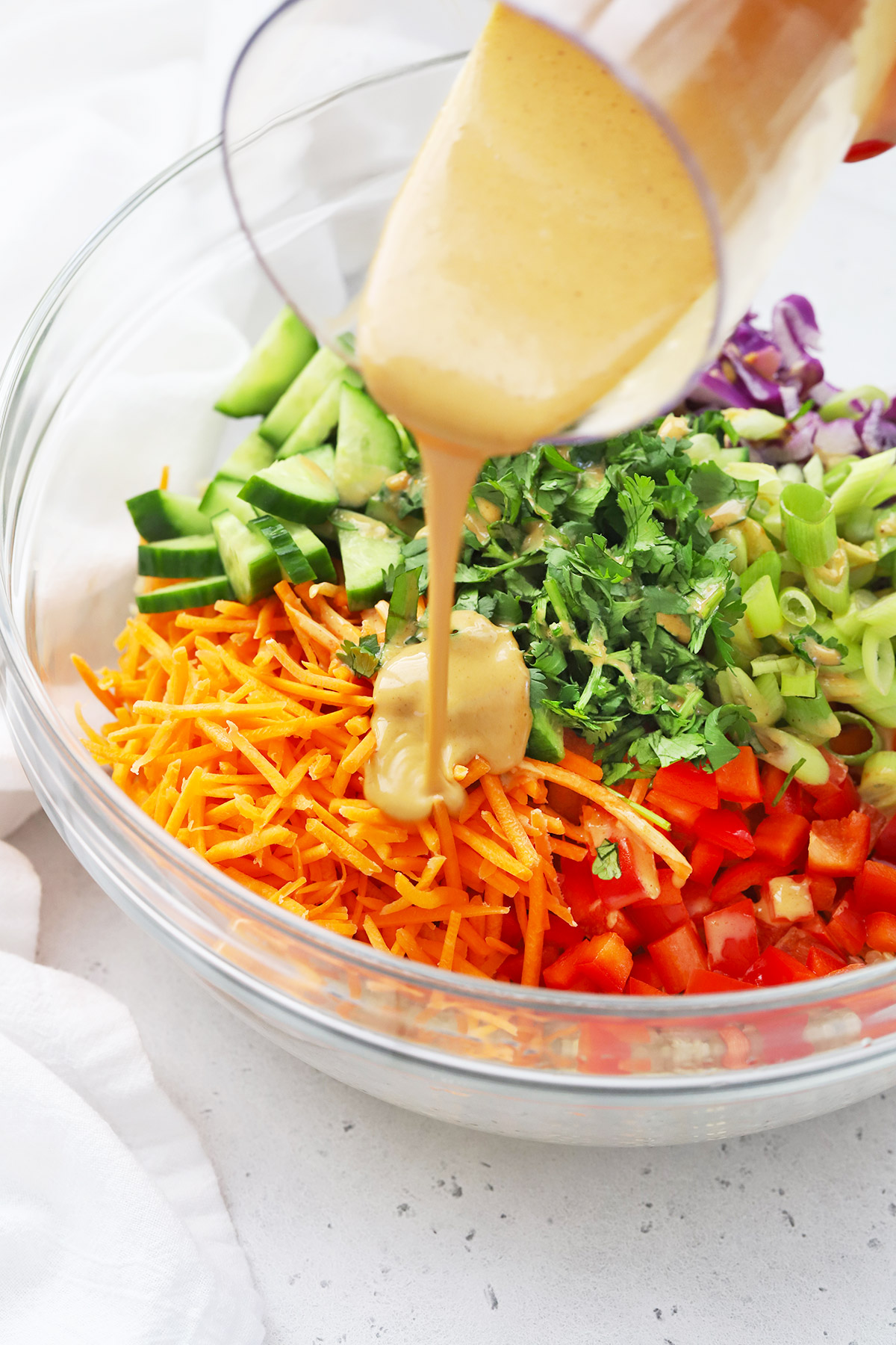 Pouring Peanut Dressing on Thai Quinoa Salad in a glass bowl