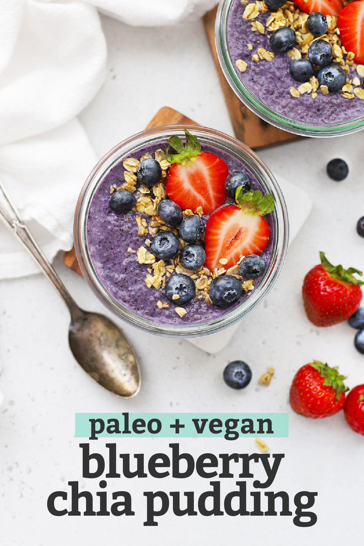 "Blueberry chia pudding topped with fresh berries and granola with text overlay that reads ""Vegan + Paleo Blueberry Chia Pudding"""