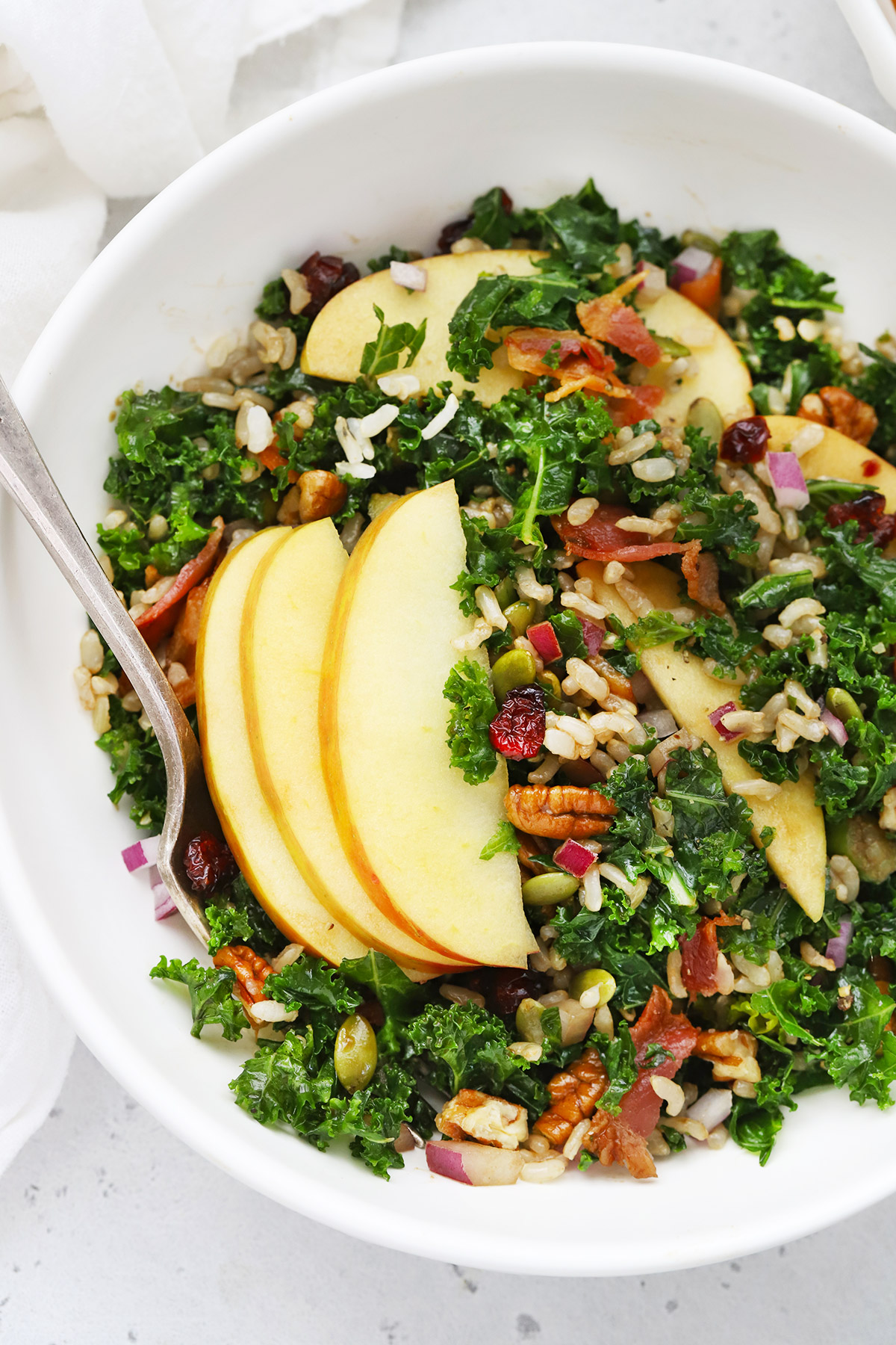 Close up overhead view of White bowl of Harvest Apple Kale Salad with Balsamic Dressing