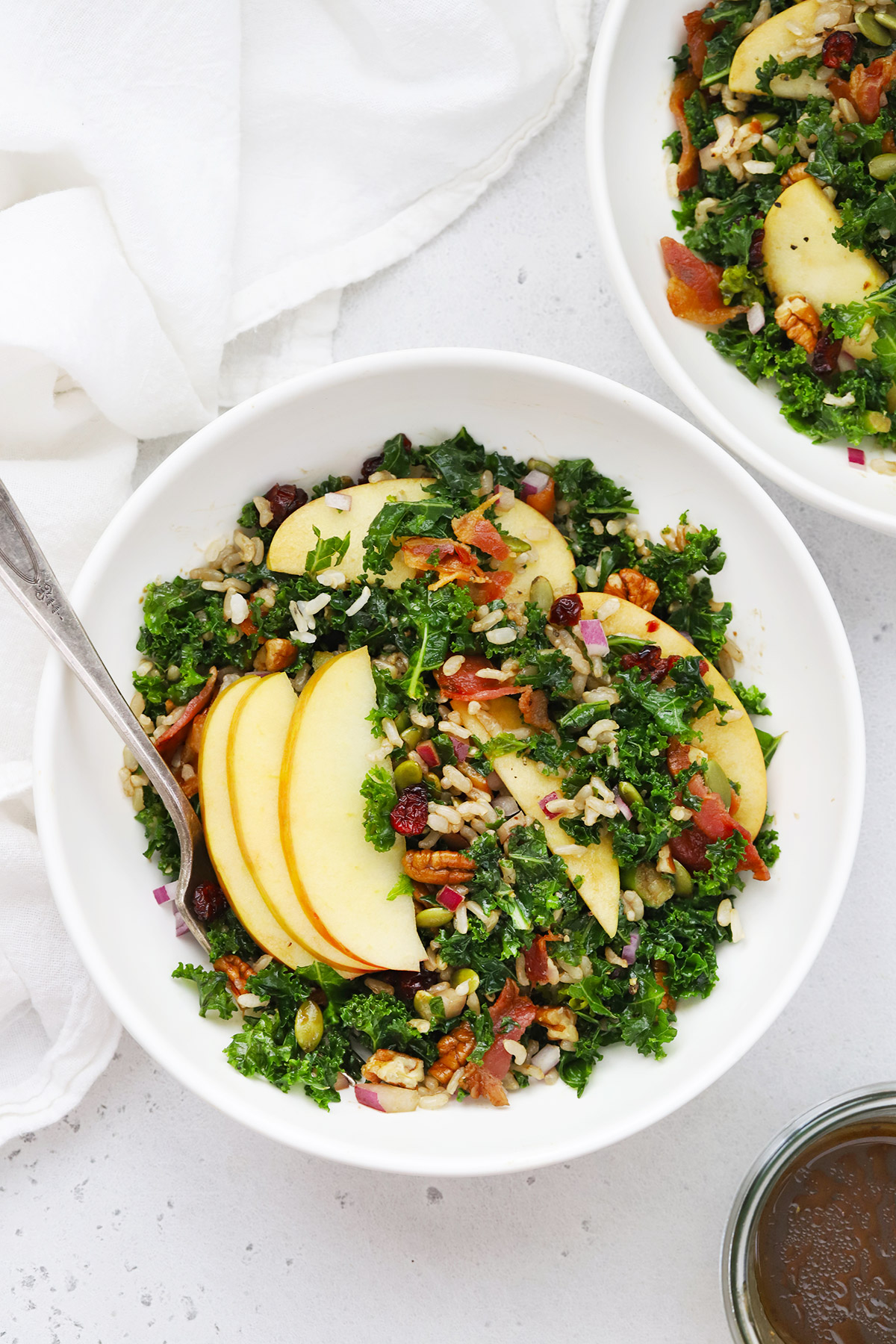 Overhead view of two bowls of Harvest Apple Kale Salad with Balsamic Dressing from One Lovely Life